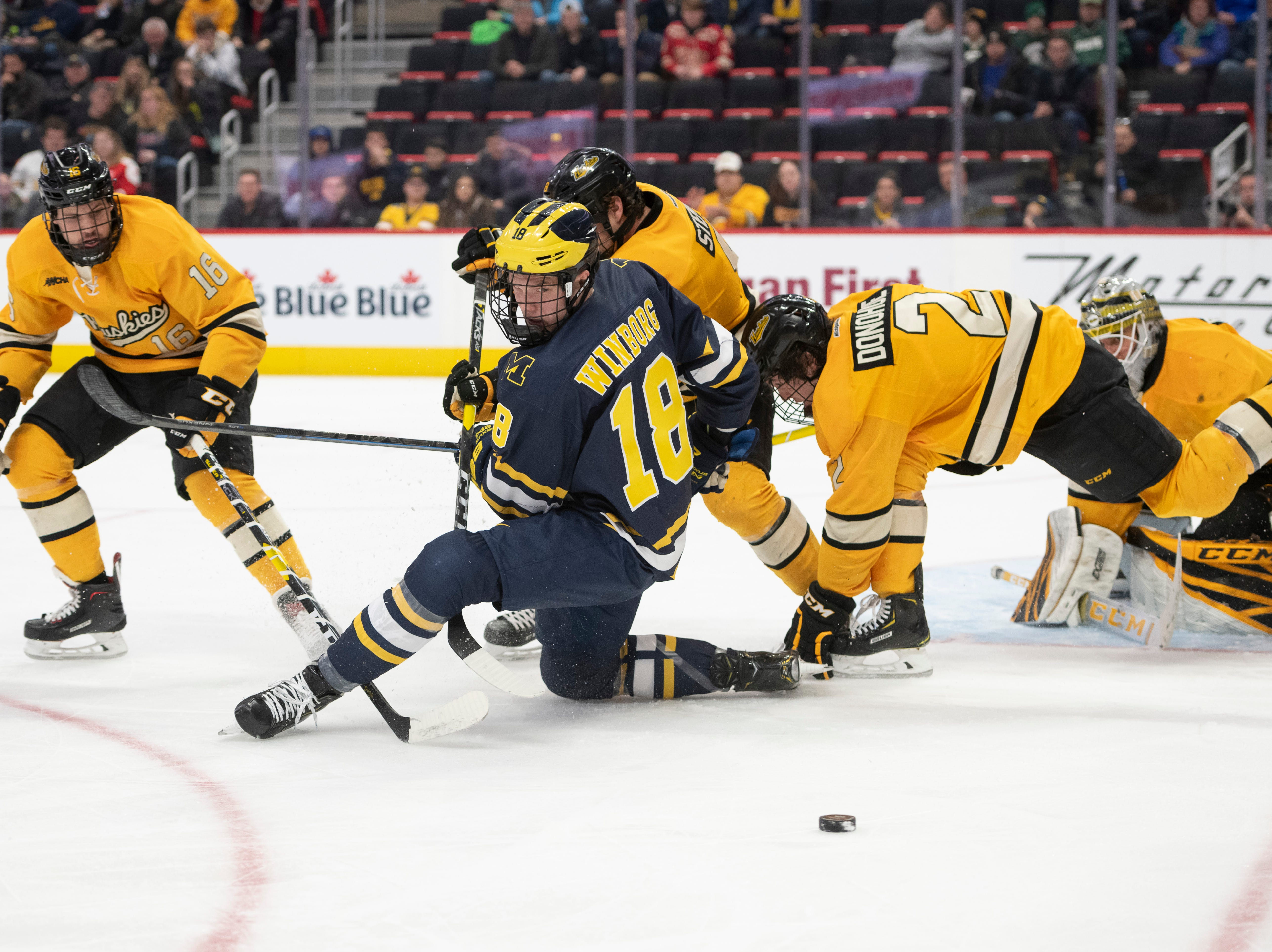Michigan forward Adam Winborg tries to control a loose puck in front of Michigan Tech's net in the second period.