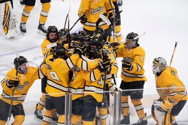 The Michigan Tech Huskies celebrate their shootout win over Michigan.