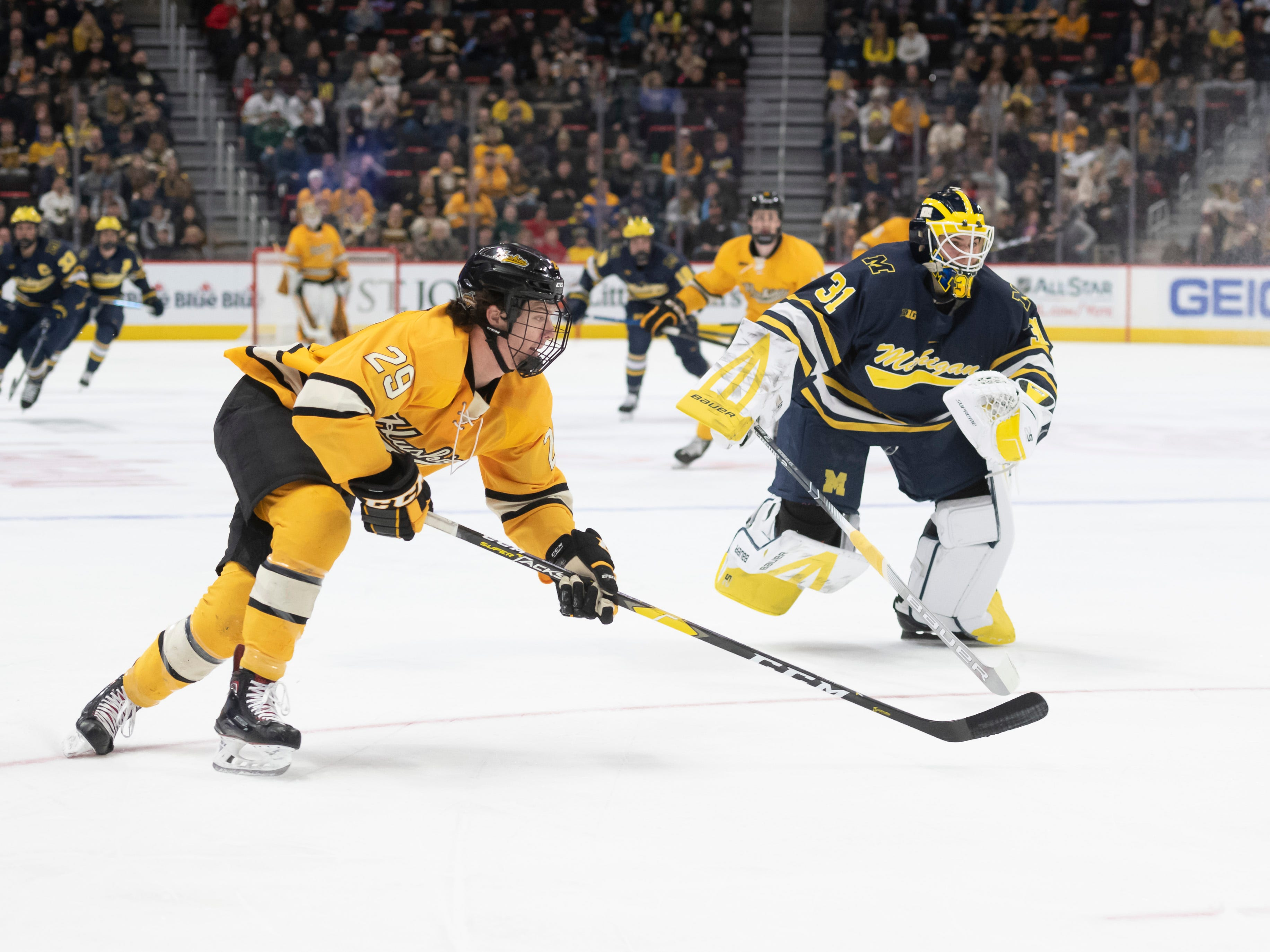 Michigan goaltender Strauss Mann is way out of the net while trying to keep Michigan Tech forward Alec Broetzman from scoring in the first period.
