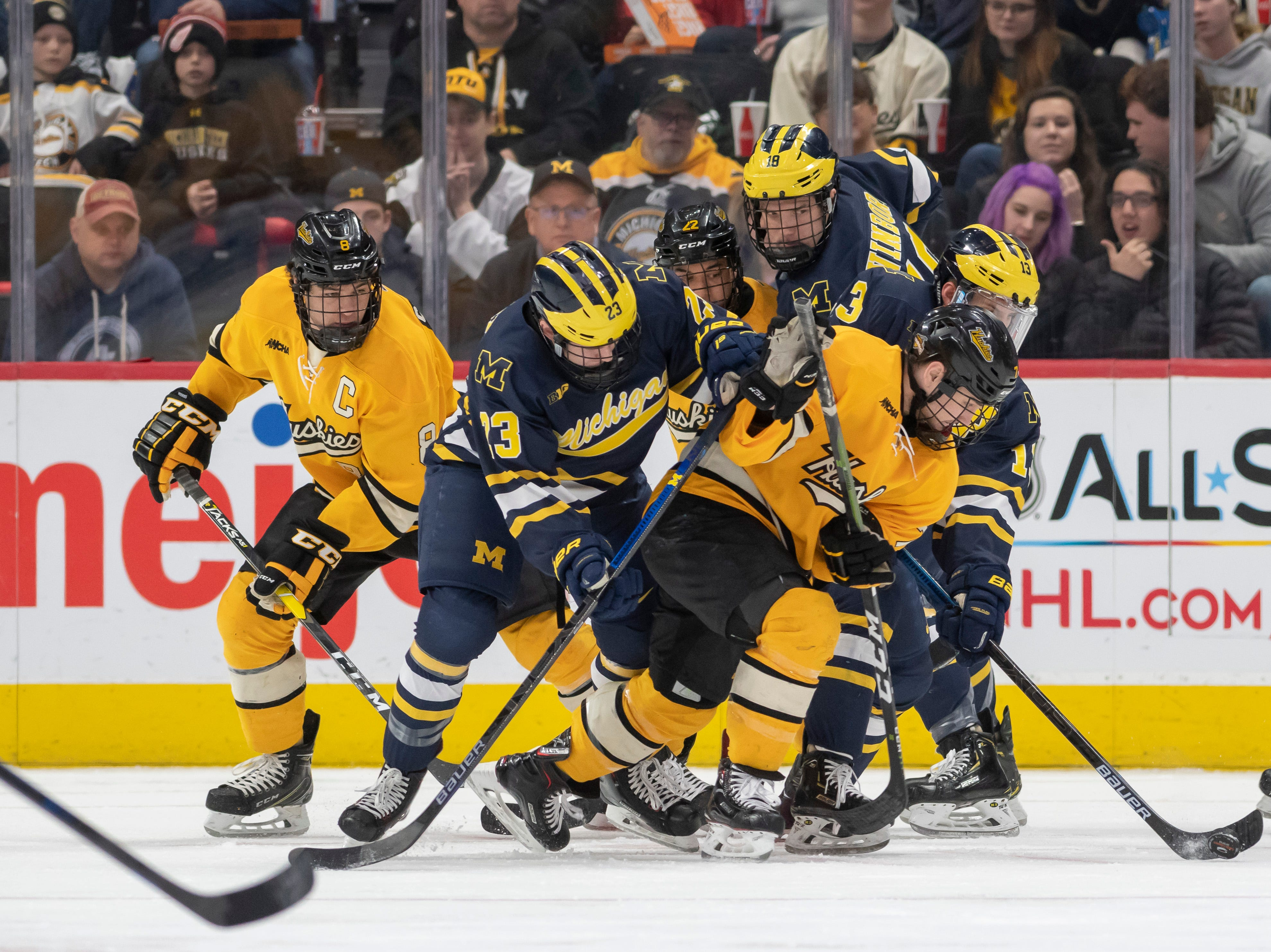 Michigan and Michigan Tech battle for the puck in the first period.