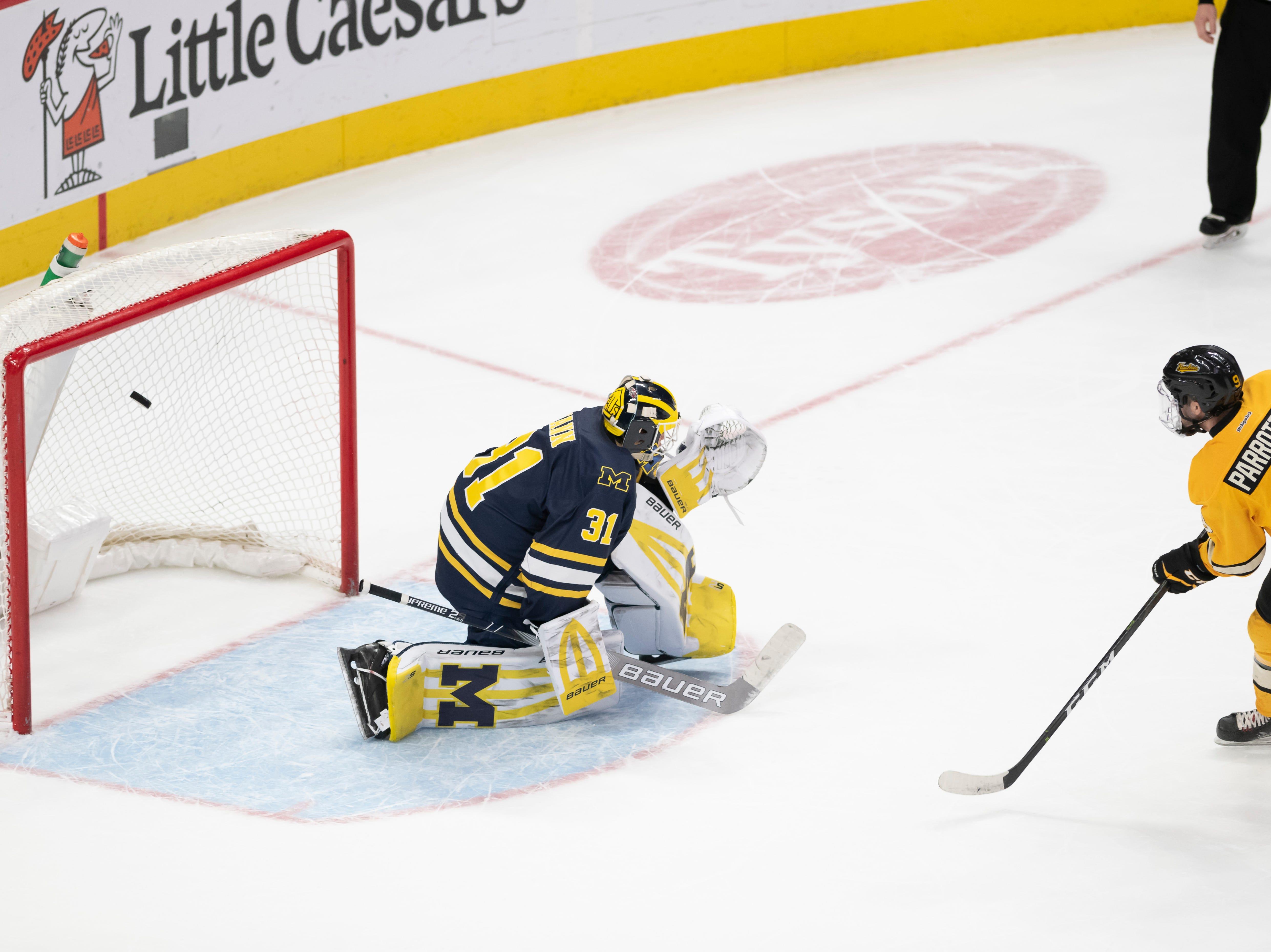 Michigan Tech forward Tommy Parrottino scores the game winning goal on Michigan goaltender Strauss Mann during the shootout.