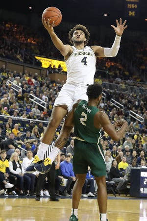 Isaiah Livers of the Michigan Wolverines drives to the basket against Chancellor Barnard of the Binghamton Bearcats during the first half.
