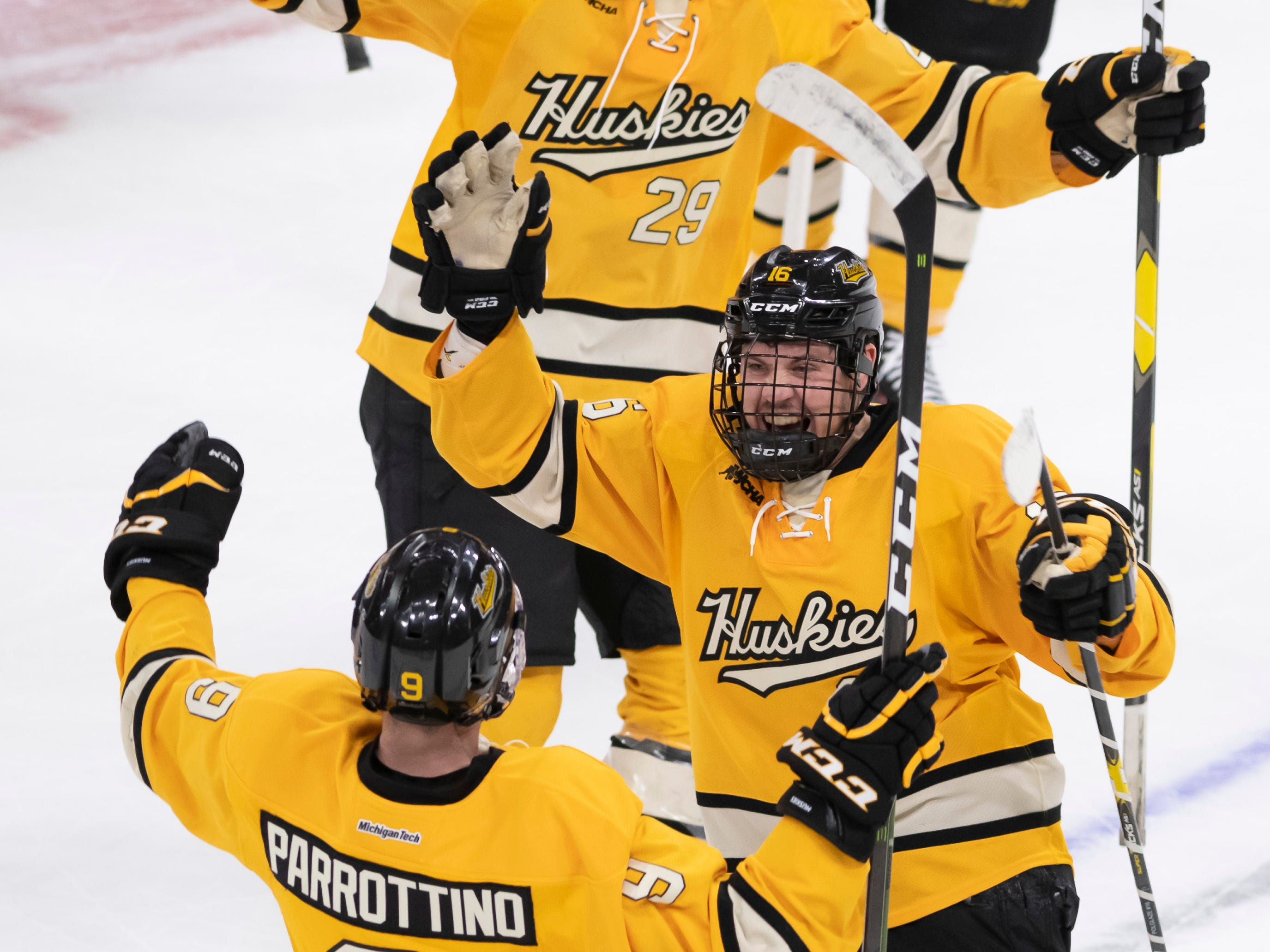 Michigan Tech forward Tommy Parrottino (9) celebrates with his teammates after scoring the winning goal in the shootout.