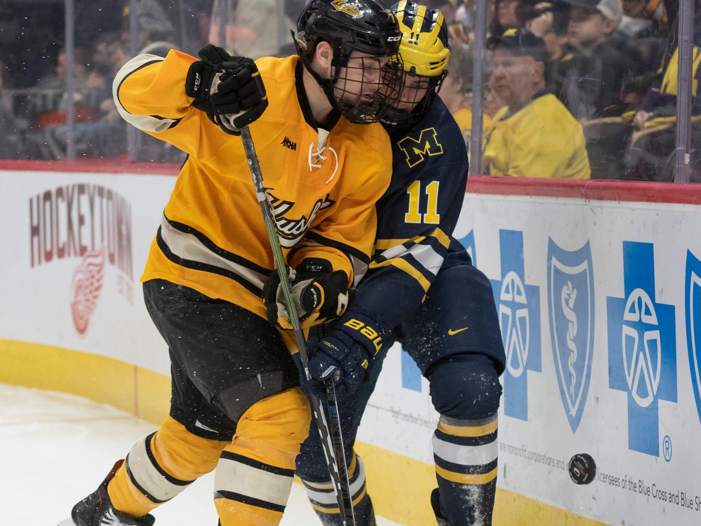 Michigan Tech defenseman Keegan Ford and Michigan forward Brendan Warren battle for the puck in the second period.