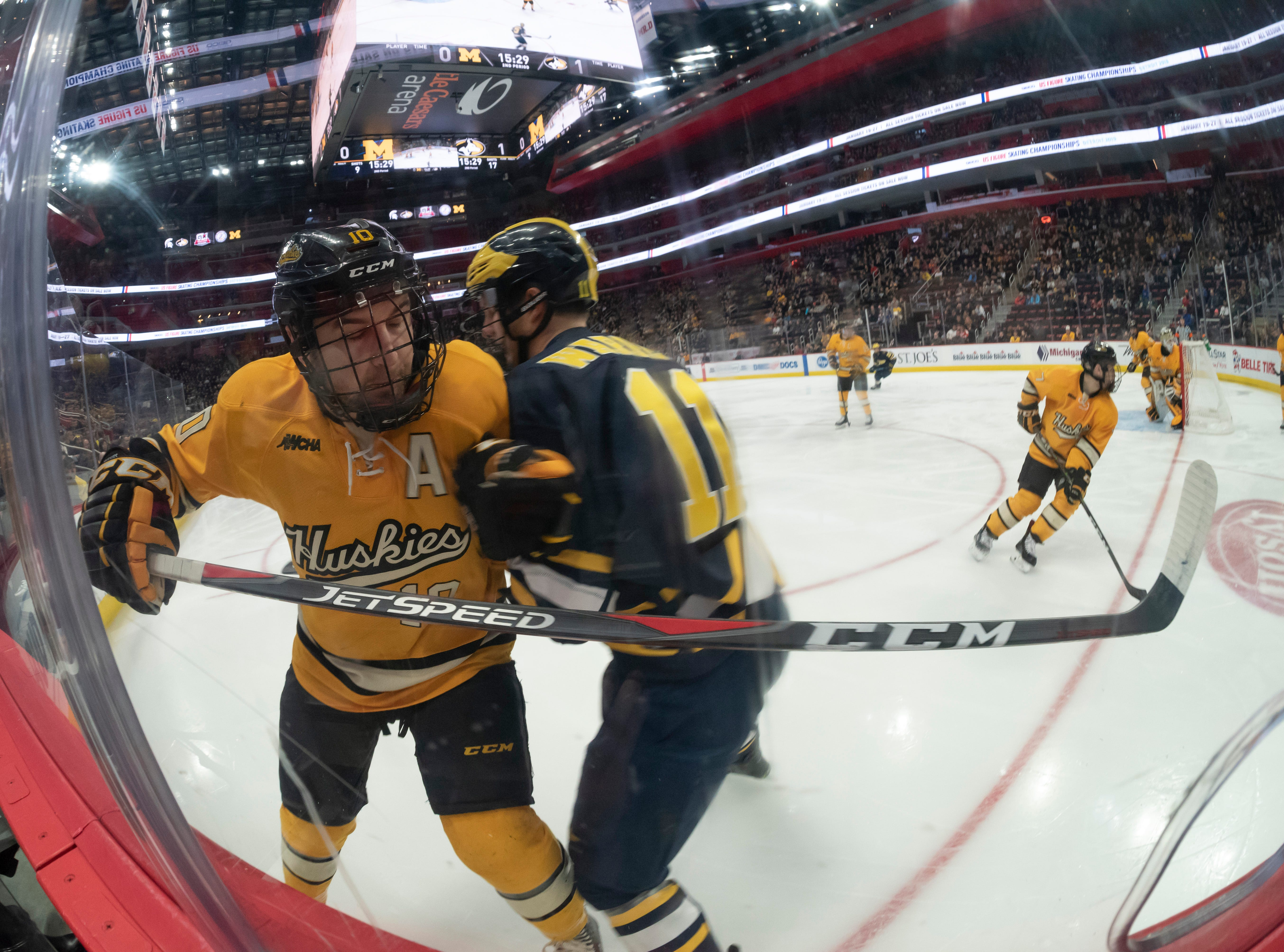 Michigan Tech forward Jake Jackson and Michigan forward Brendan Warren check each other along the boards in the second period.