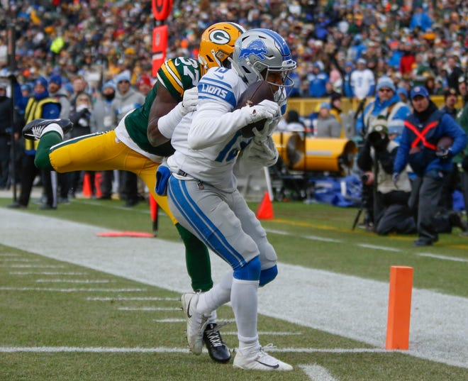 Detroit's T.J. Jones catches a touchdown pass in front of Green Bay's Josh Jackson during the second half Sunday.