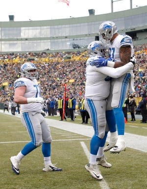 The Detroit Lions' Levine Toilolo celebrates his touchdown catch on a fake field goal during the first half.