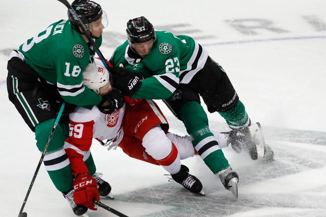 Detroit Red Wings left wing Tyler Bertuzzi is squeezed by Dallas Stars center Tyler Pitlick (18) and defenseman Esa Lindell (23) during the first period on Saturday night.