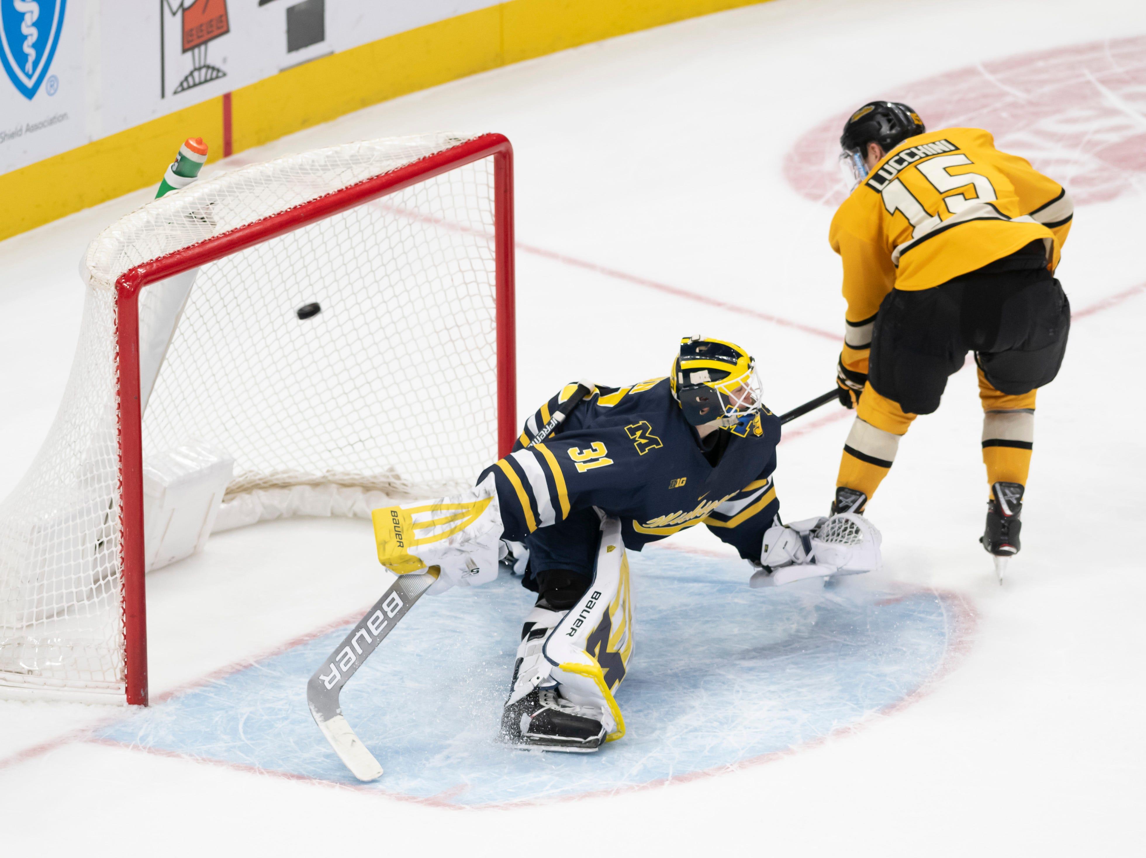 Michigan Tech forward Jake Lucchini scores on Michigan goaltender Strauss Mann during the shootout.