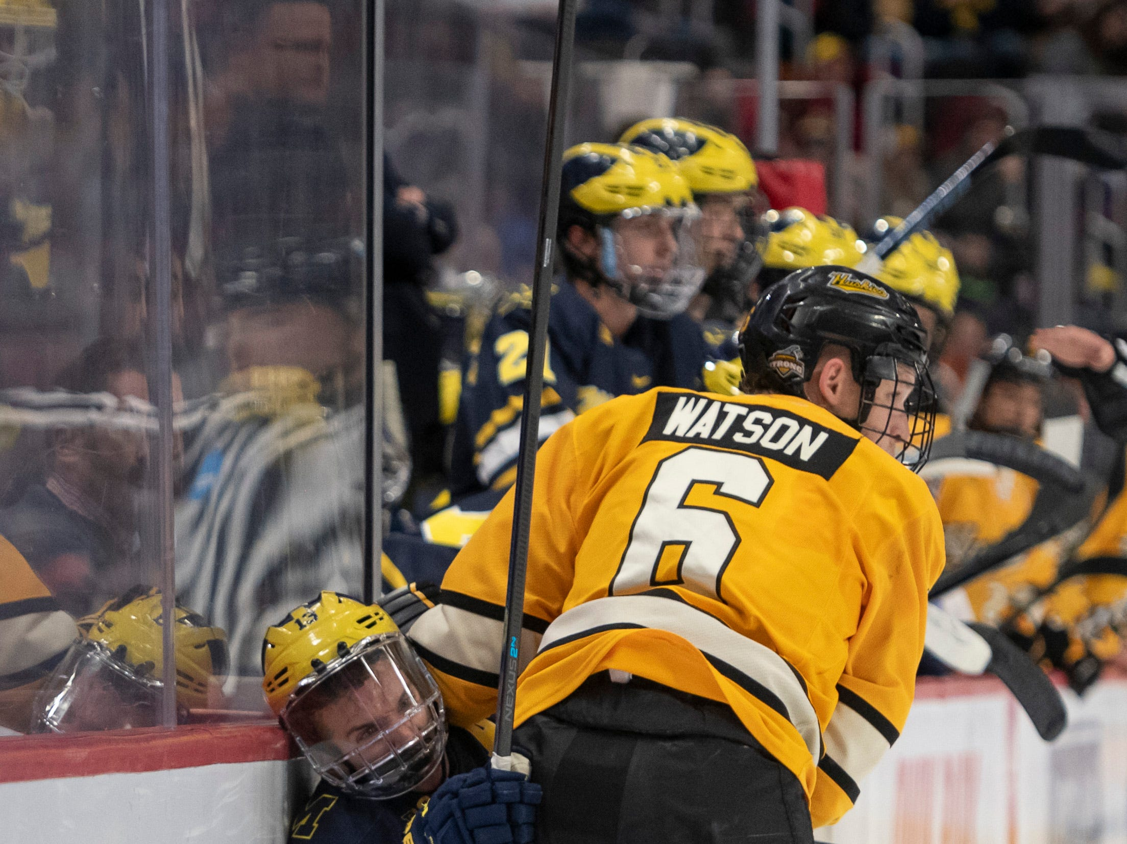 Michigan forward Jake Slaker is checked into the boards by Michigan Tech defenseman Cooper Watson in the second period.