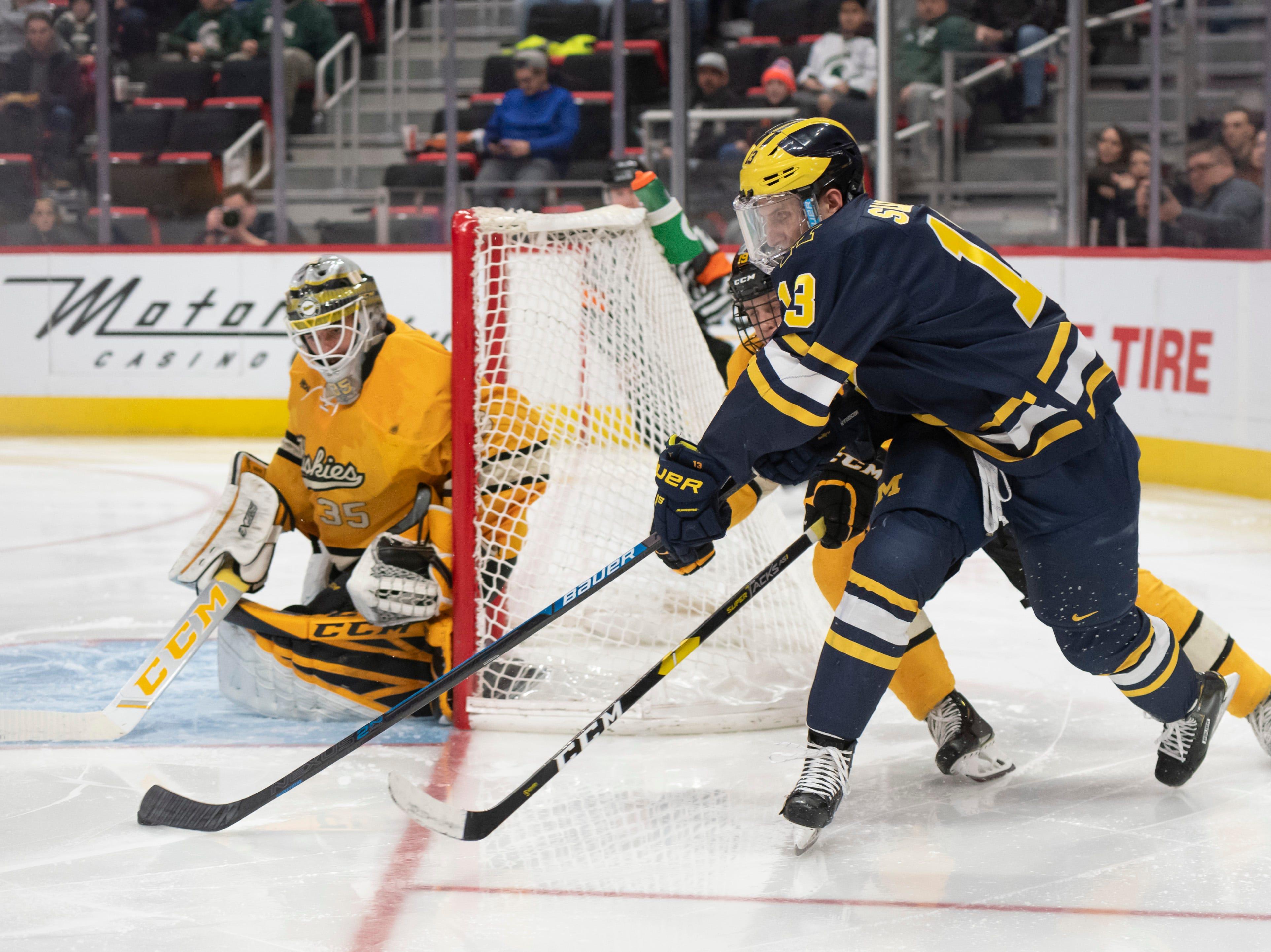 Michigan forward Jake Slaker tries to wrap the puck around Michigan Tech goaltender Robbie Beydoun in the second period.