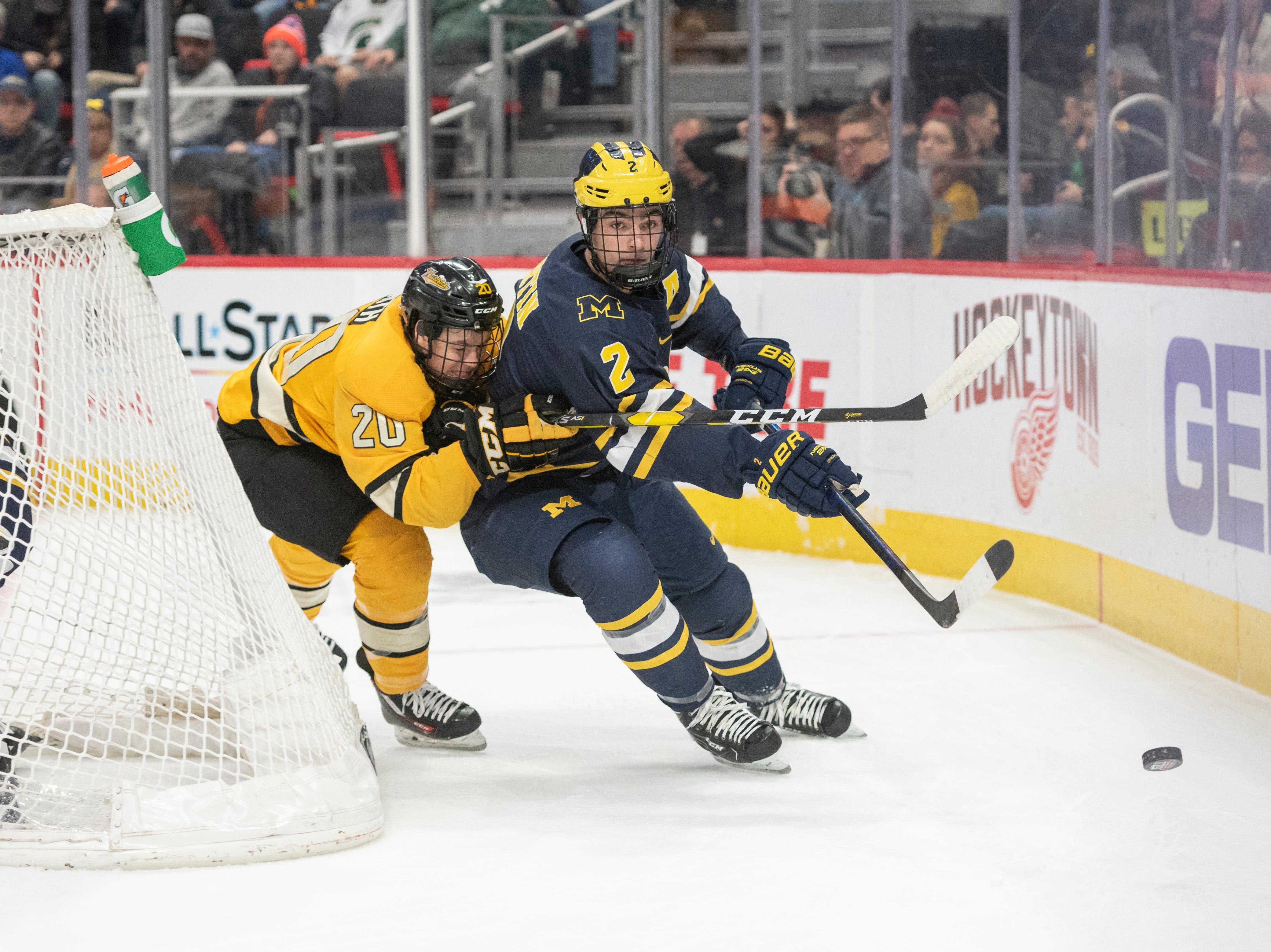 Michigan Tech forward Alex Smith and Michigan defenseman Luke Martin battle for the puck in the first period.