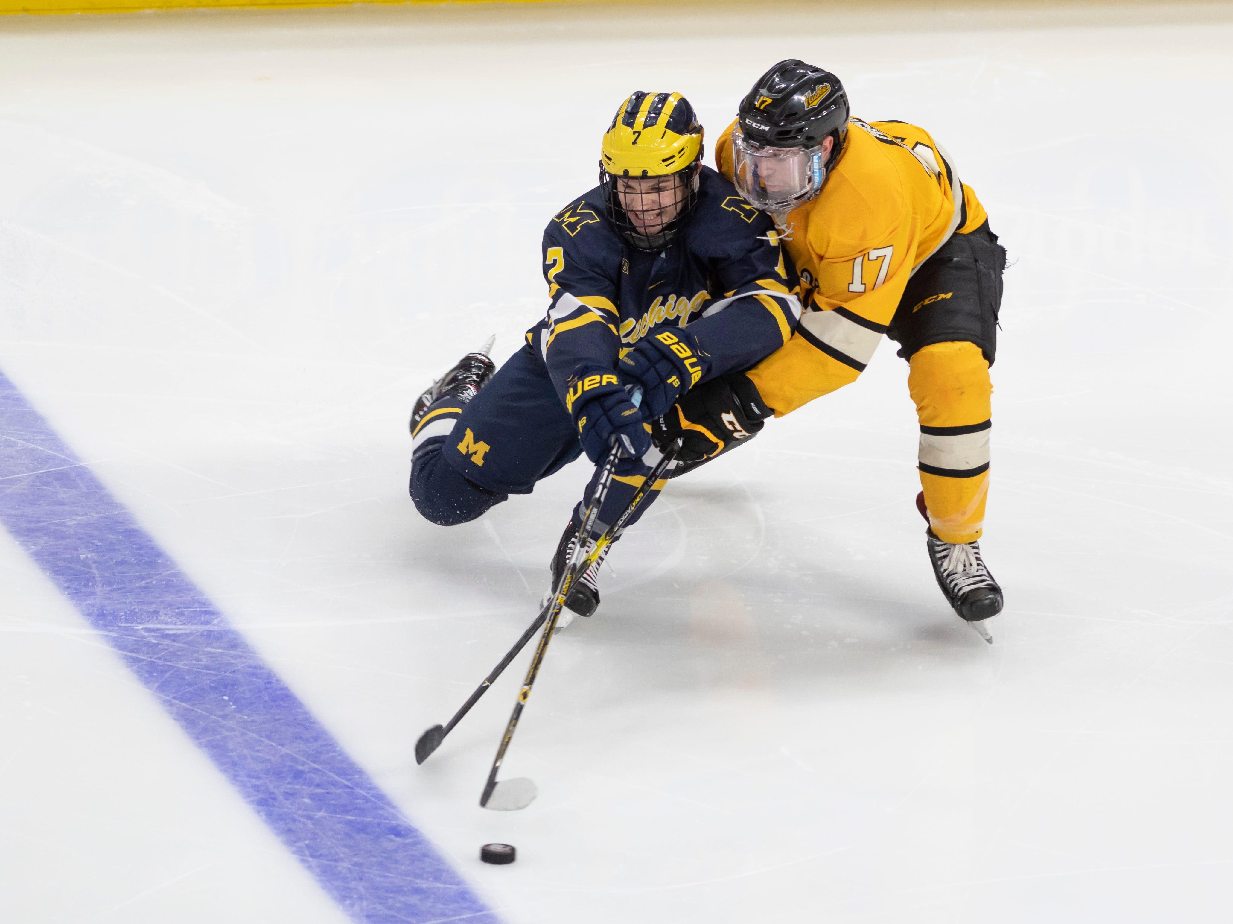 Michigan defenseman Nick Blankenburg and Michigan Tech forward Justin Misiak battle for the puck in the third period.