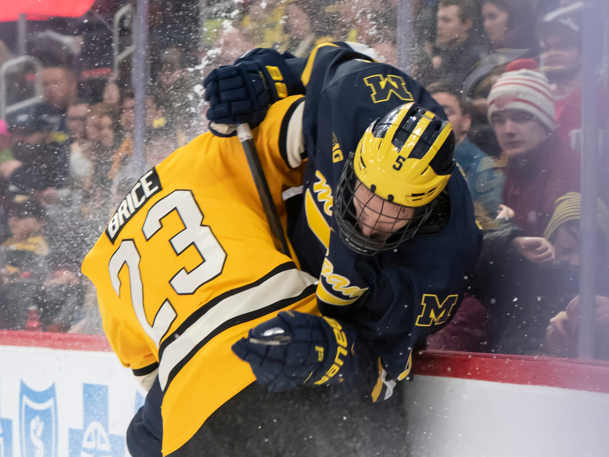 Michigan defenseman Griffin Luce gets checked into the boards by Michigan Tech forward Raymond Brice in the first period.