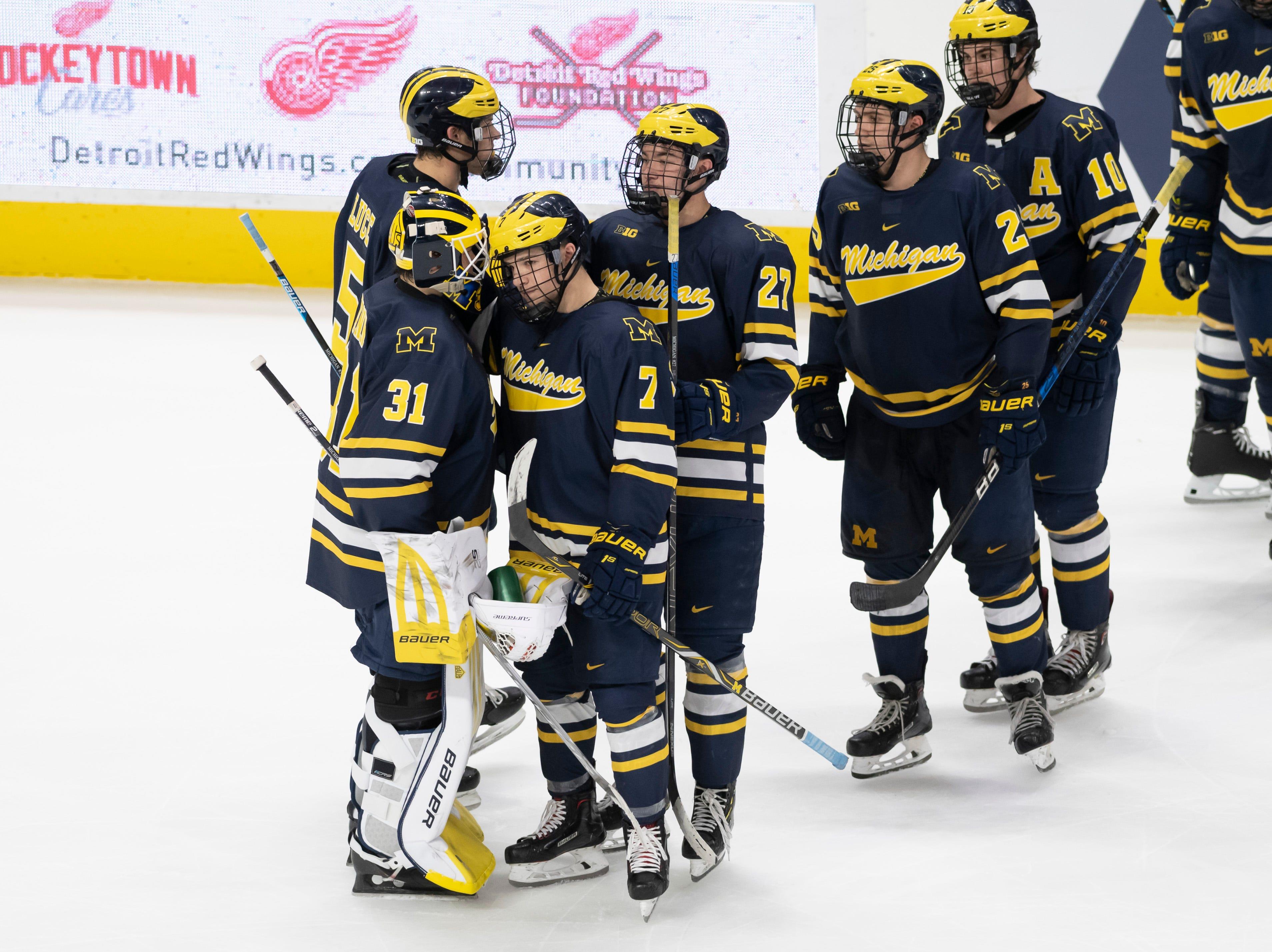Michigan consoles goaltender Strauss Mann after losing to Michigan Tech in a shootout.