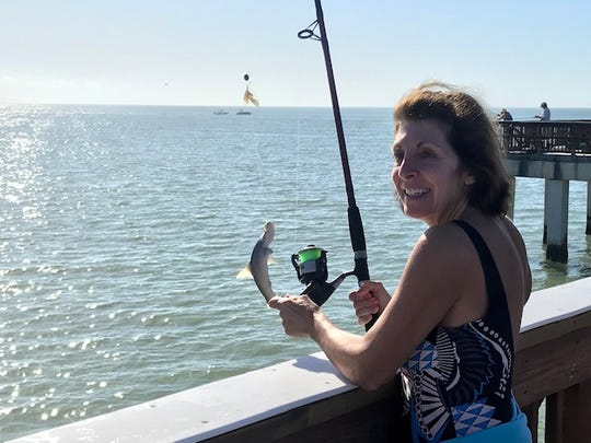 Gail Brunalt, of Massachusetts, reels in a baby hammerhead shark off the Fort Myers Beach pier Sunday.