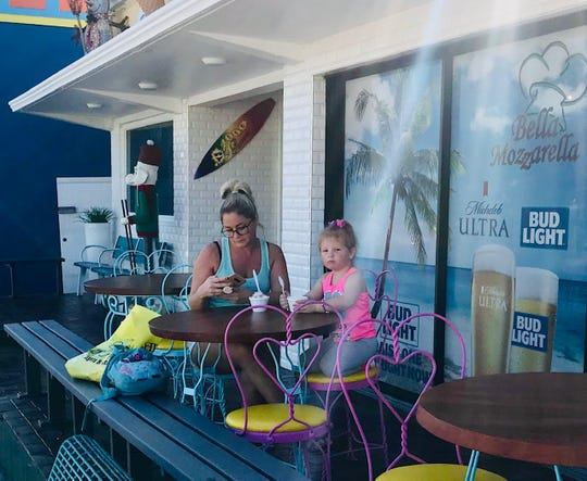 Lynette and Kinsley Bomtrager, of Indiana, cool off with ice cream from 2000 Flavors on Fort Myers Beach.