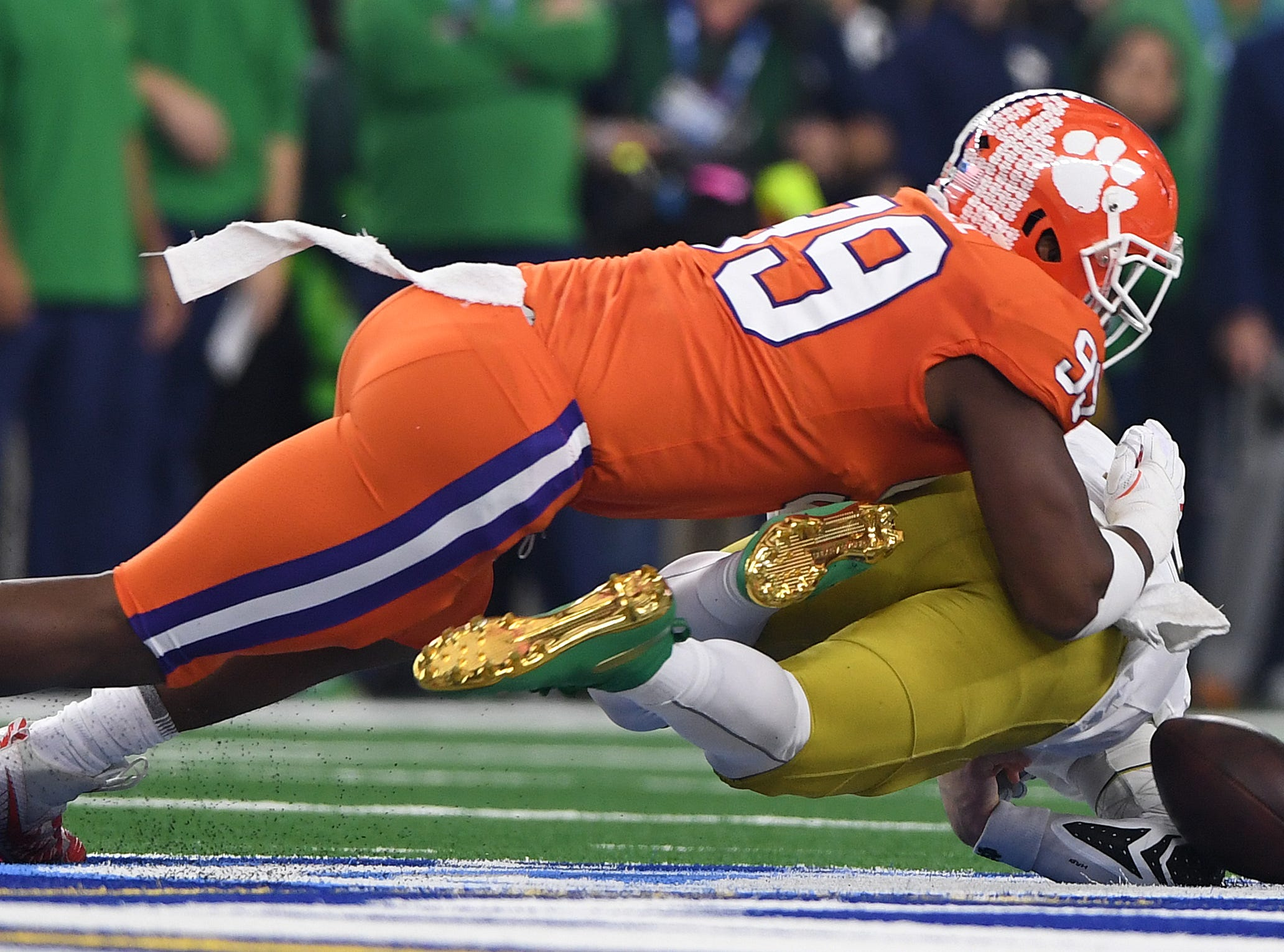 Clemson defensive lineman Clelin Ferrell (99) brings down Notre Dame quarterback Ian Book (12) during the 1st quarter of the Goodyear Cotton Bowl at AT&T stadium in Arlington, TX Saturday, December 29, 2018.