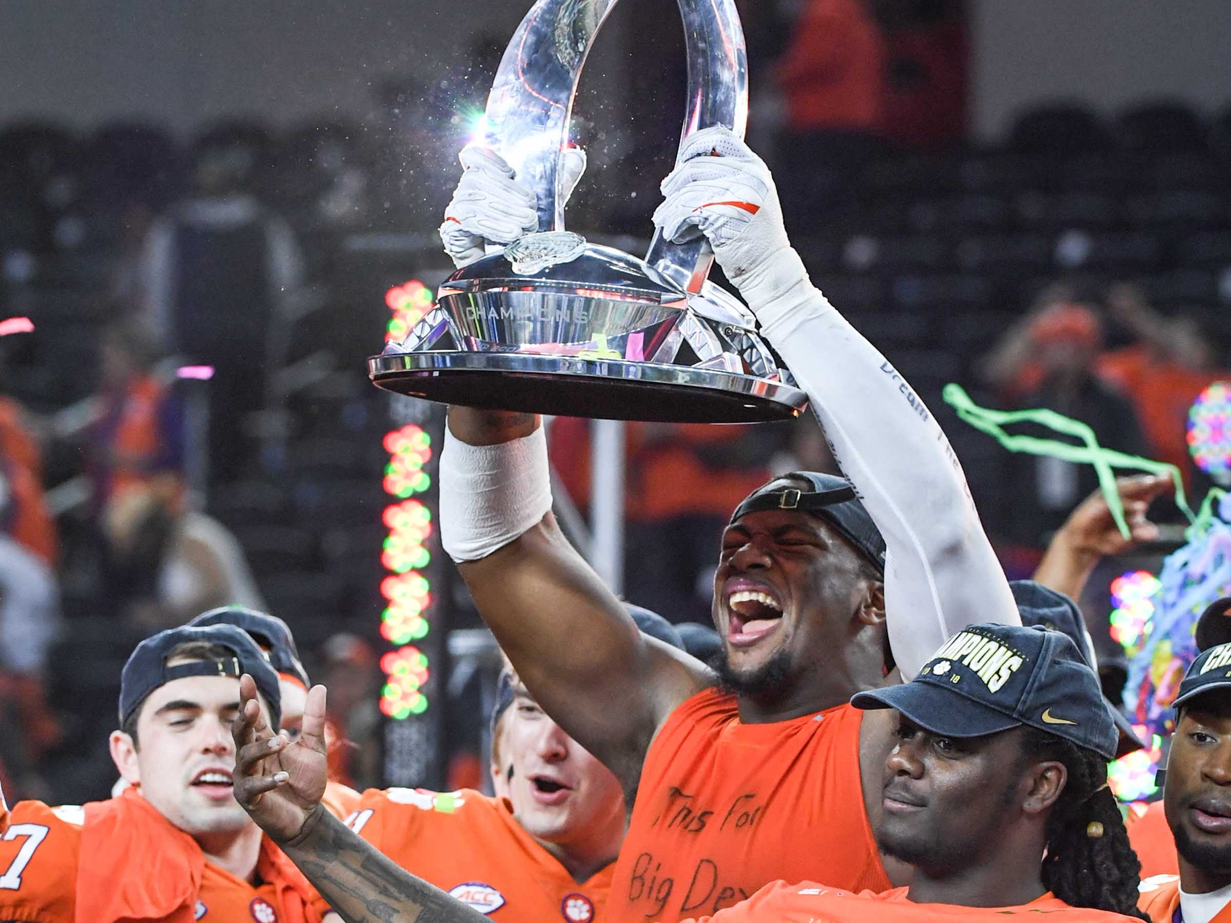 """Clemson defensive lineman Clelin Ferrell (99), wearing an undershirt with handwritten words """"This For Big Dex"""", holds up the trophy after their 30-3 win over Notre Dame in the College Football Playoff Semifinal at the Goodyear Cotton Bowl Classic at AT&T Stadium in Arlington, Texas Saturday, December 29, 2018."""