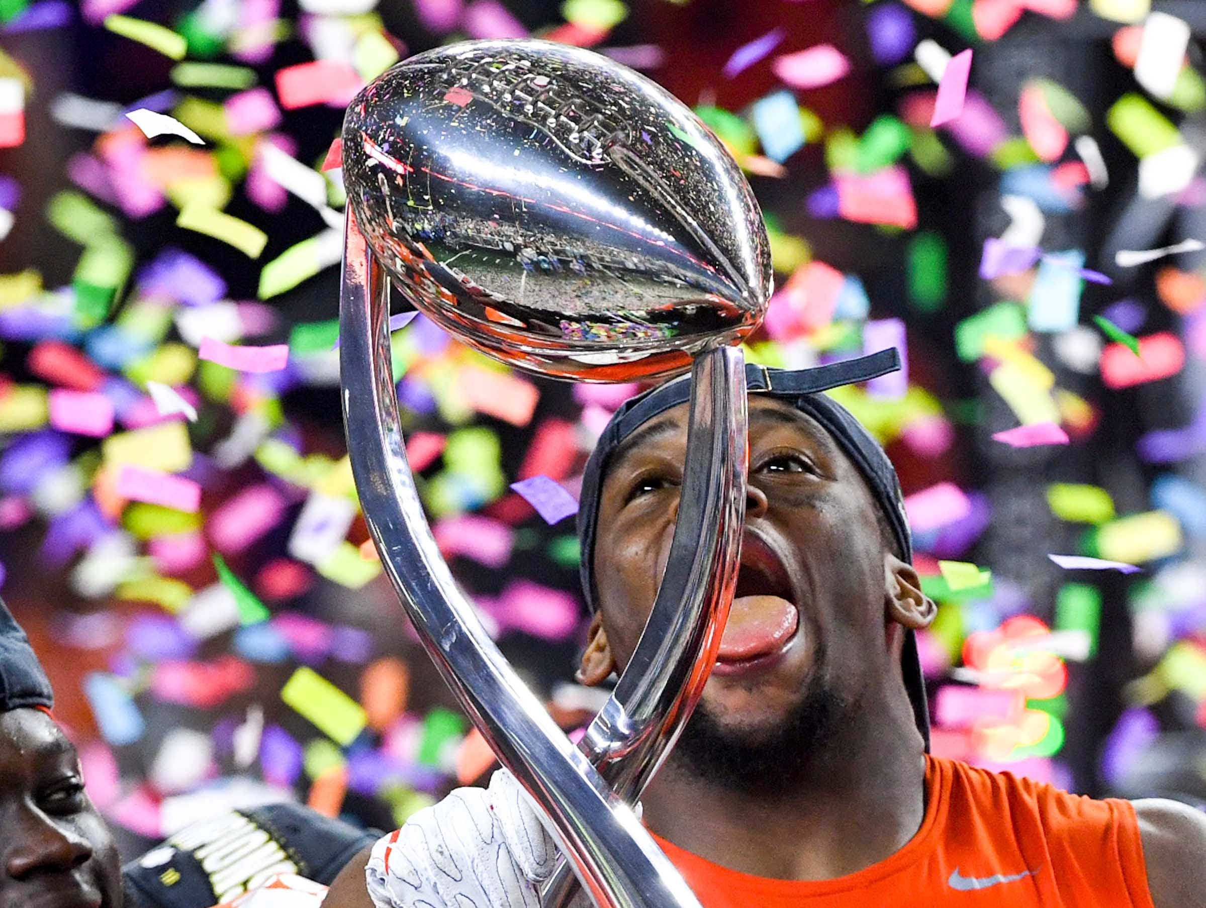 Clemson defensive lineman Clelin Ferrell (99) pretends to lick the trophy after the College Football Playoff Semifinal 30-3 win over Notre Dame at the Goodyear Cotton Bowl Classic at AT&T Stadium in Arlington, Texas Saturday, December 29, 2018.