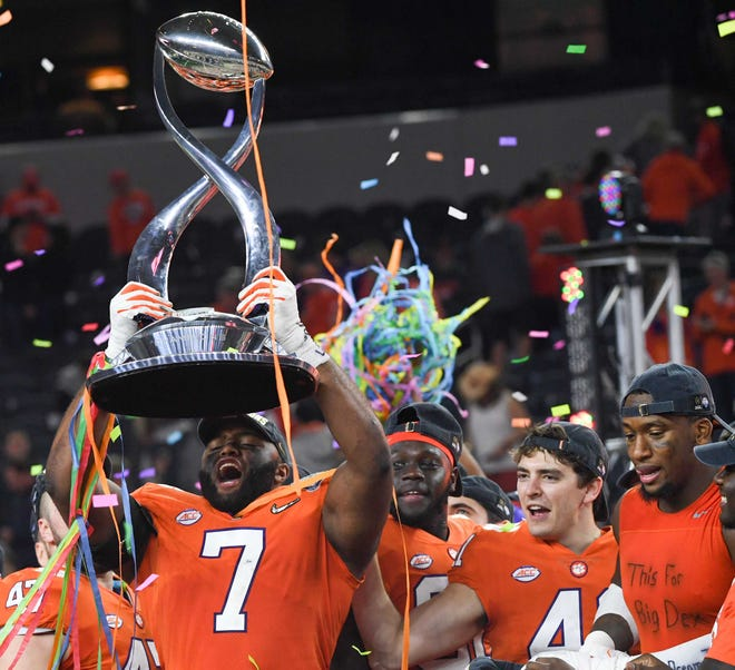 "Clemson defensive lineman Austin Bryant (7), left, holds up the Cotton Bowl trophy near defensive lineman Clelin Ferrell (99), right, wearing an undershirt with handwritten words ""This For Big Dex"", after their 30-3 win over Notre Dame in the College Football Playoff Semifinal at the Goodyear Cotton Bowl Classic at AT&T Stadium in Arlington, Texas Saturday, December 29, 2018."