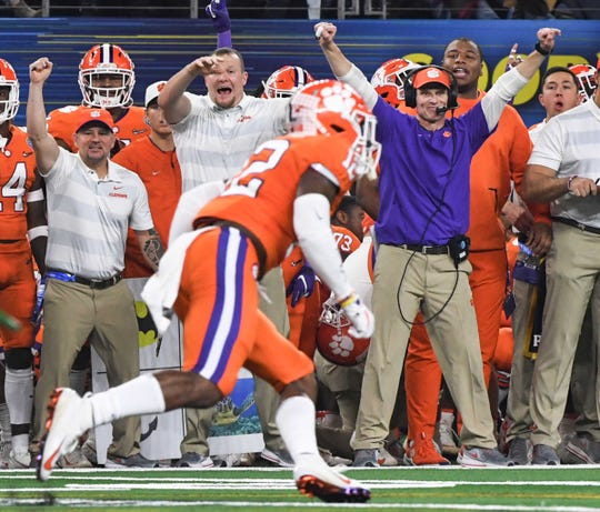 Clemson Defensive Coordinator Brent Venables raises his arms up and smiles as safety Nolan Turner (24) returns an interception during the fourth quarter of the College Football Playoff Semifinal at the Goodyear Cotton Bowl Classic at AT&T Stadium in Arlington, Texas Saturday, December 29, 2018. Clemson defense only allowed Notre Dame a field goal and no touchdowns.