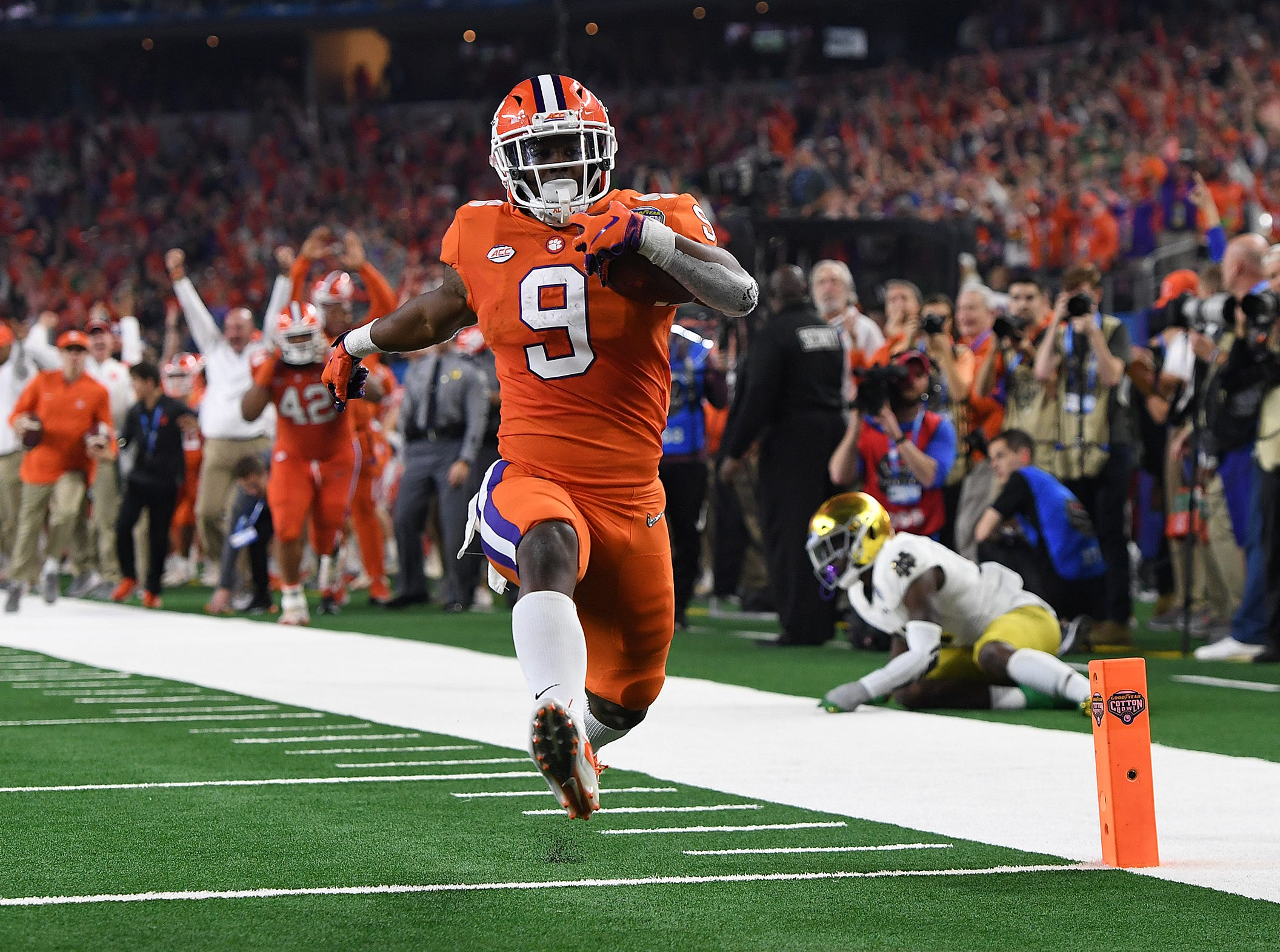 Clemson running back Travis Etienne (9) high steps it into the end zone on a 62 yard TD carry against Notre Dame during the third quarter of the Goodyear Cotton Bowl at AT&T stadium in Arlington, Texas on Saturday.