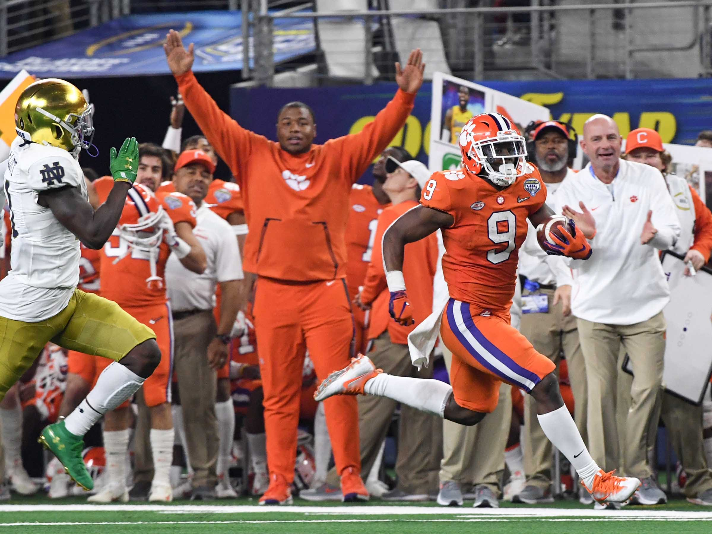 Clemson defensive lineman Dexter Lawrence (90) raises his arms on the sidelines as Clemson running back Travis Etienne (9) runs 61-yards during the third quarter of the College Football Playoff Semifinal at the Goodyear Cotton Bowl Classic at AT&T Stadium in Arlington, Texas Saturday, December 29, 2018.