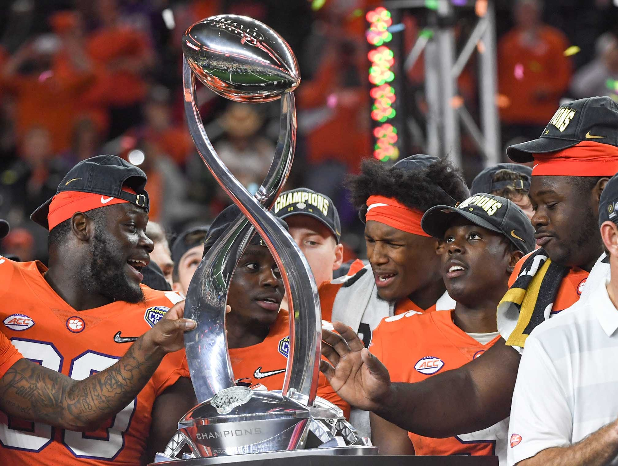 Clemson cornerback Trayvon Mullen (1) , left, tight end Milan Richard (80), wide receiver Tee Higgins (5), running back Travis Etienne (9), and defensive lineman Albert Huggins (67) hold the trophy after their 30-3 win over Notre Dame in the College Football Playoff Semifinal at the Goodyear Cotton Bowl Classic at AT&T Stadium in Arlington, Texas Saturday, December 29, 2018.