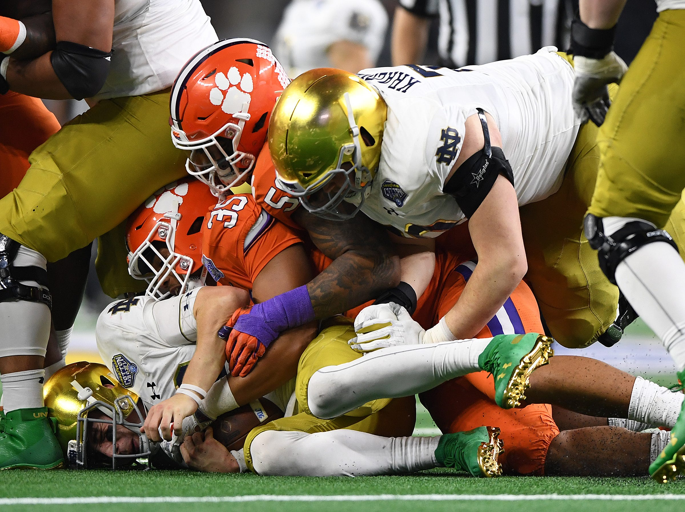 Clemson linebacker Justin Foster (35) brings down Notre Dame quarterback Ian Book (12) during the 4th quarter of the Goodyear Cotton Bowl at AT&T stadium in Arlington, TX Saturday, December 29, 2018.