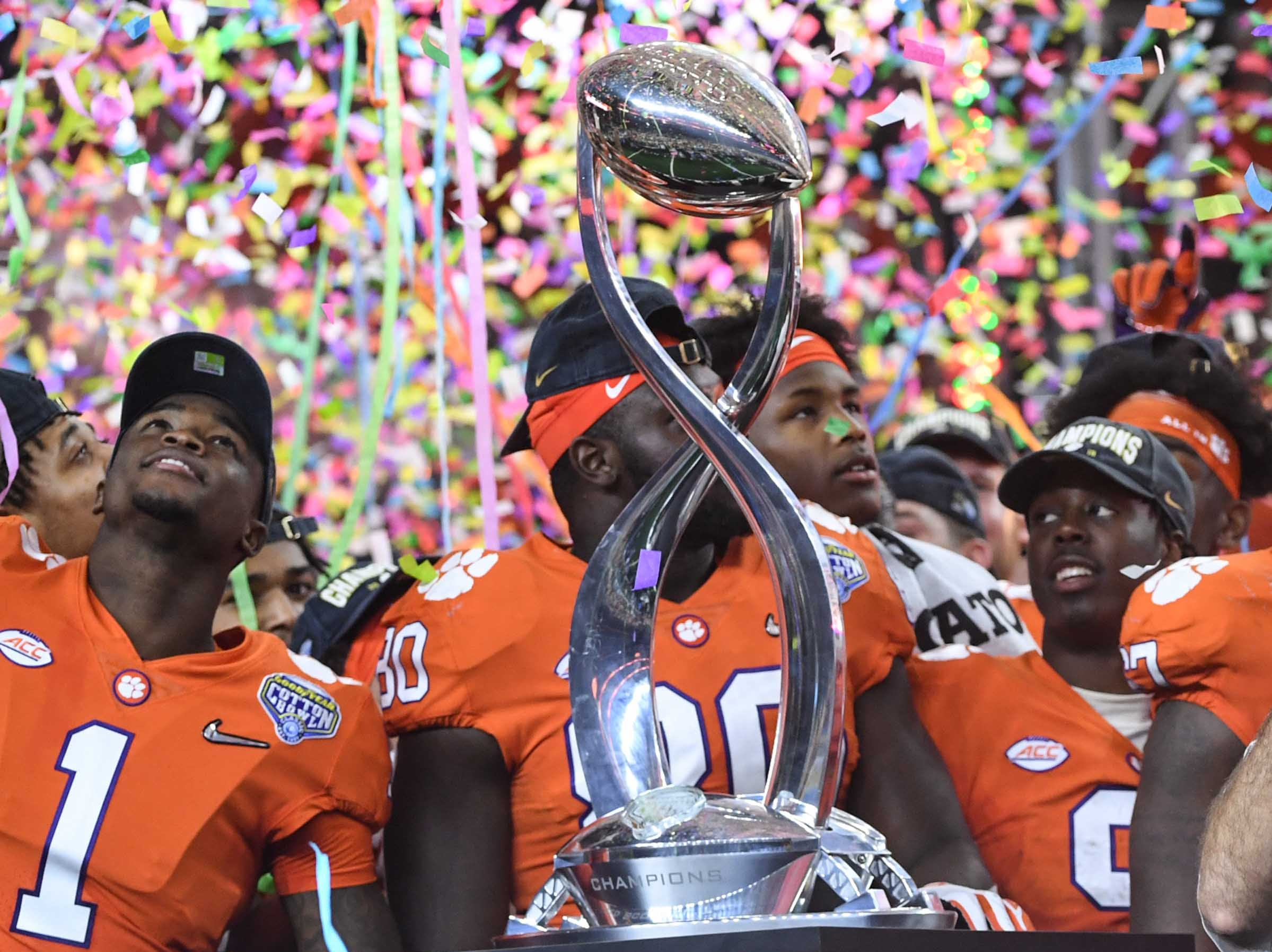 Clemson cornerback Trayvon Mullen (1) , left, tight end Milan Richard (80), and running back Travis Etienne (9) are showered with confetti after their 30-3 win over Notre Dame in the College Football Playoff Semifinal at the Goodyear Cotton Bowl Classic at AT&T Stadium in Arlington, Texas Saturday, December 29, 2018.