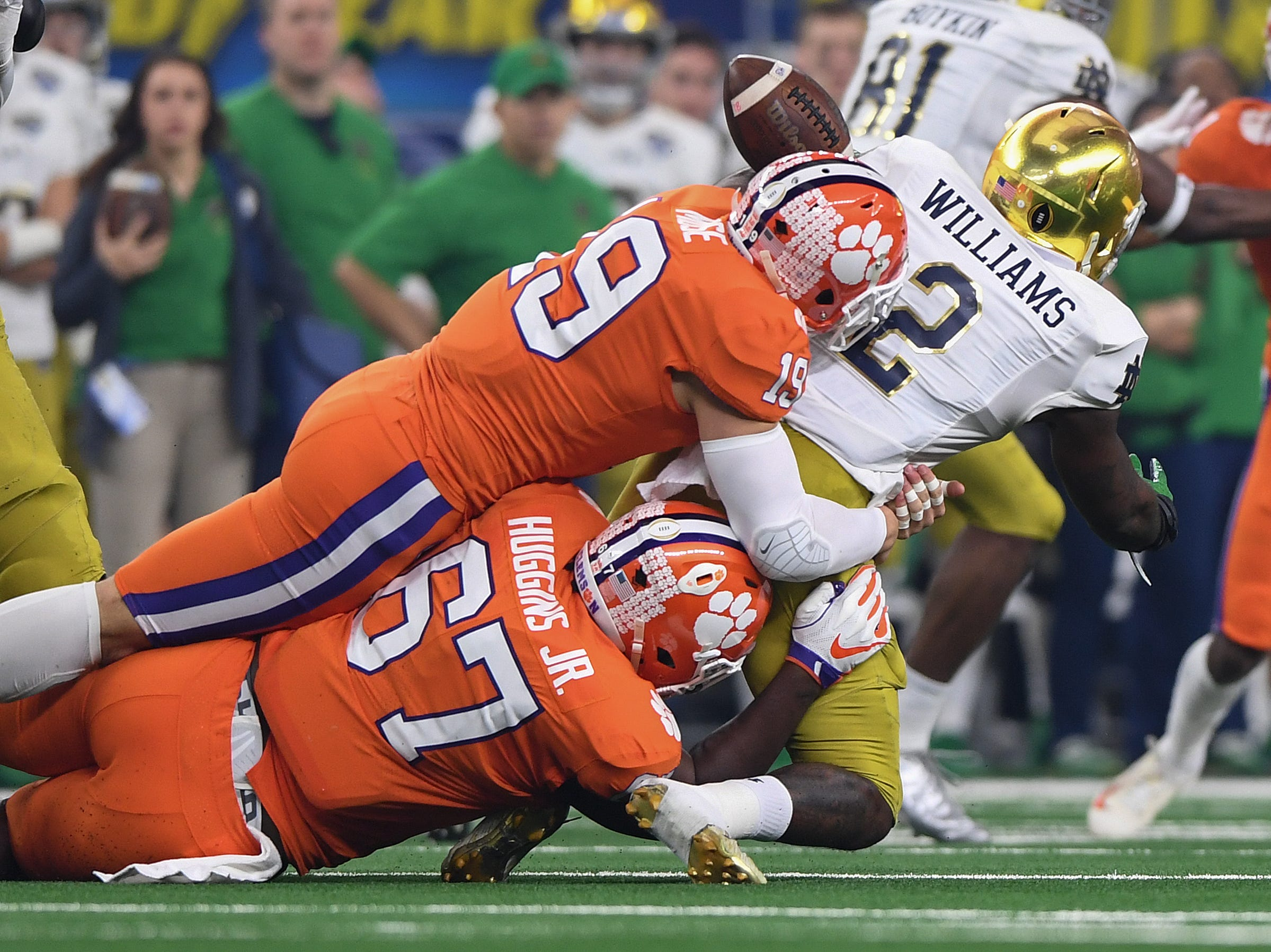 Clemson defensive back Tanner Muse (19) and defensive lineman Albert Huggins (67) bring down Notre Dame running back Dexter Williams (2) during the 1st quarter of the Goodyear Cotton Bowl at AT&T stadium in Arlington, TX Saturday, December 29, 2018.