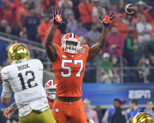 Clemson linebacker Tre Lamar (57) pressures Notre Dame quarterback Ian Book (12) during the third quarter of the College Football Playoff Semifinal at the Goodyear Cotton Bowl Classic at AT&T Stadium in Arlington, Texas Saturday, December 29, 2018.