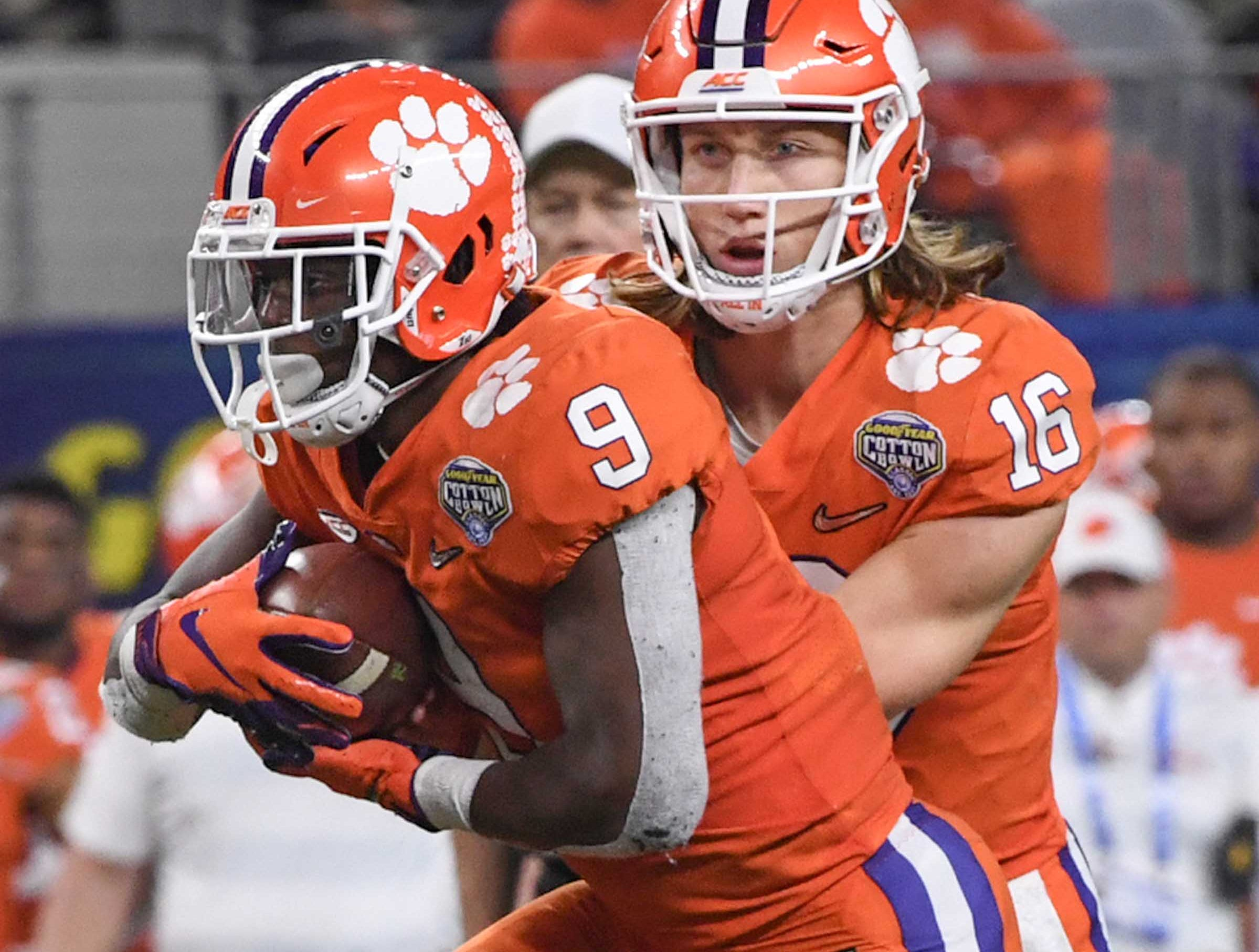 Clemson running back Travis Etienne (9) takes a handoff from quarterback Trevor Lawrence (16) during the third quarter of the College Football Playoff Semifinal at the Goodyear Cotton Bowl Classic at AT&T Stadium in Arlington, Texas Saturday, December 29, 2018.