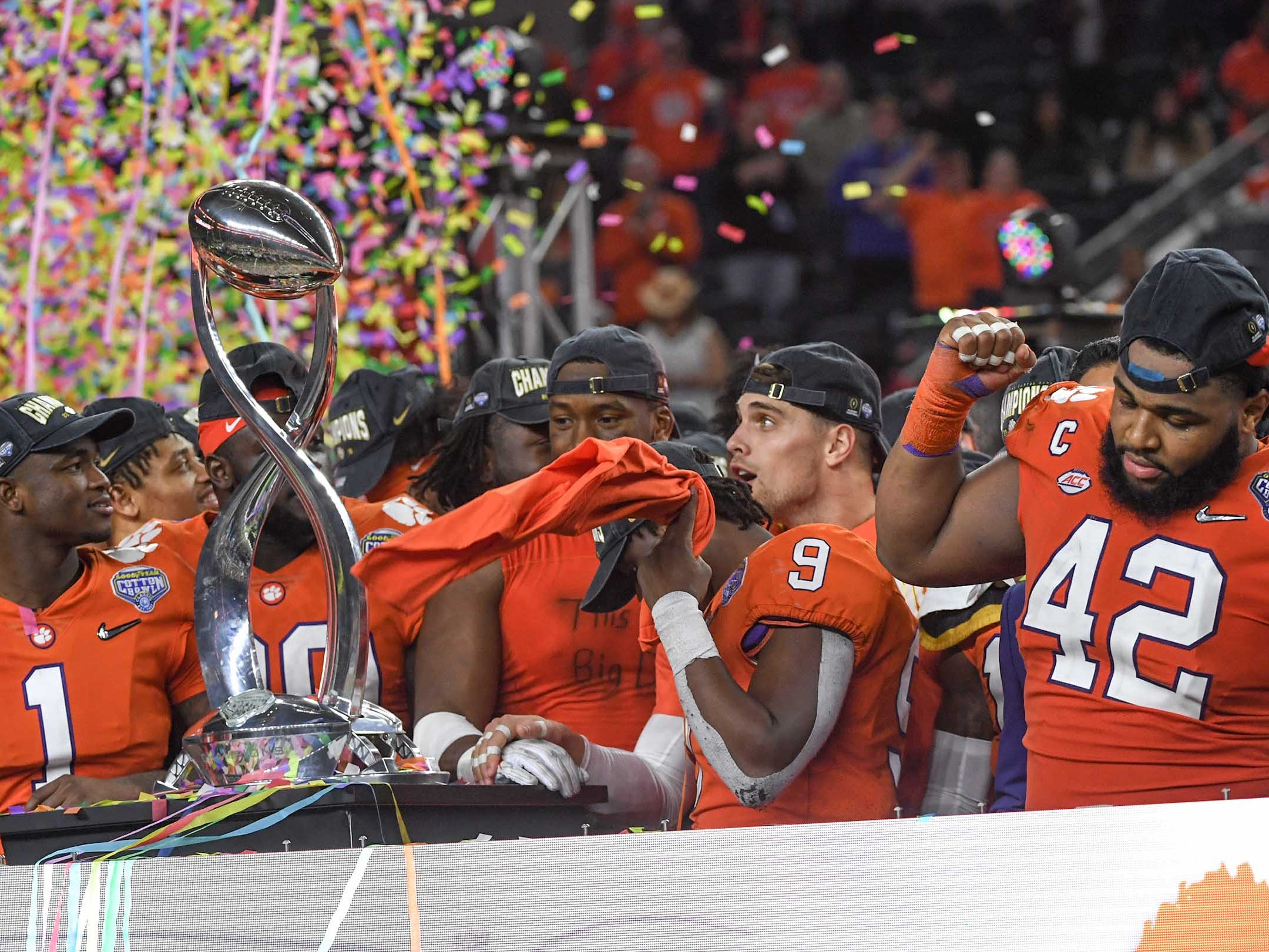 Clemson defensive lineman Christian Wilkins (42), right, dances near teammates admiring the trophy after the College Football Playoff Semifinal at the Goodyear Cotton Bowl Classic at AT&T Stadium in Arlington, Texas Saturday, December 29, 2018.