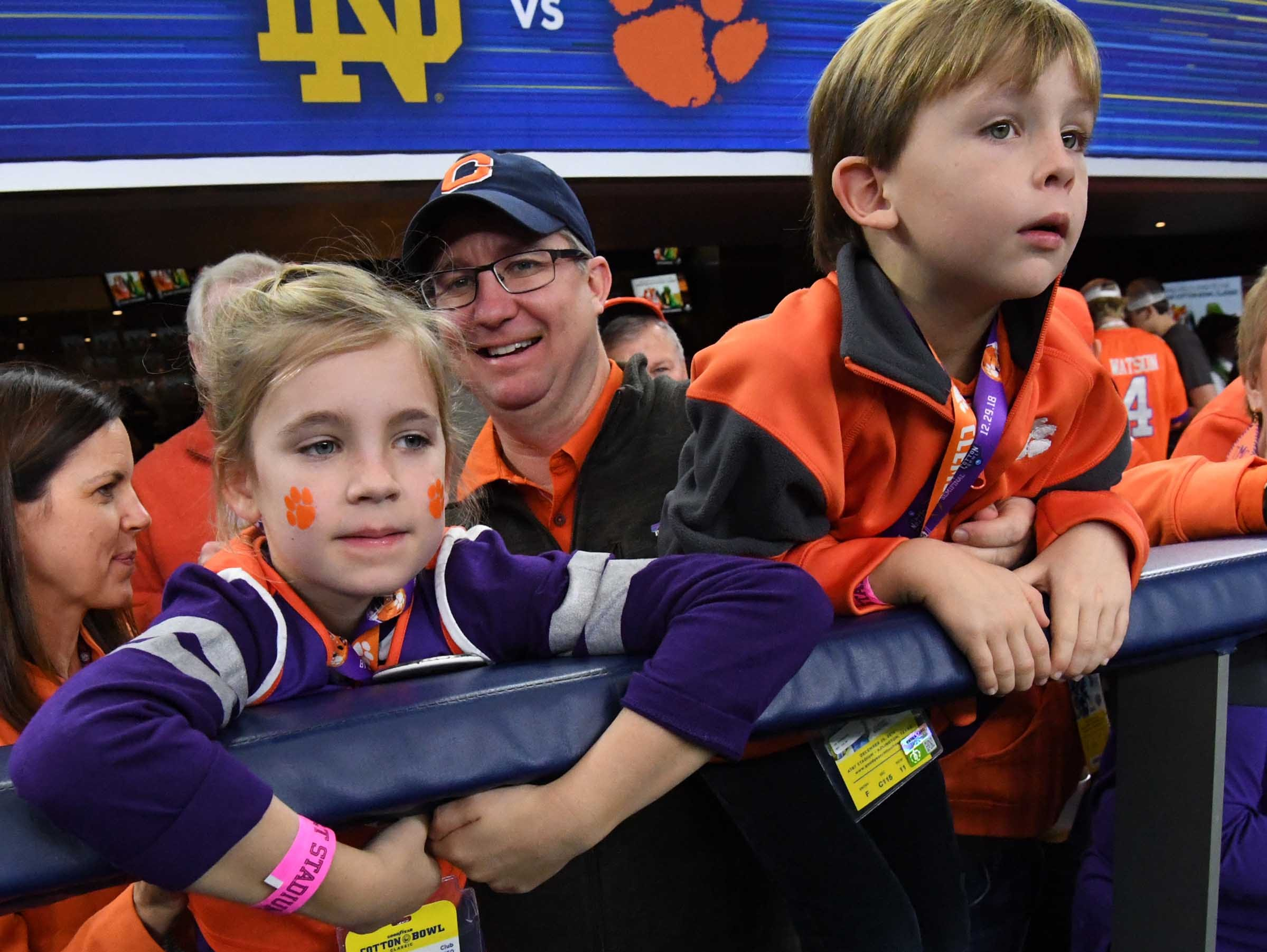 Ann Bullwinkel, left, her dad George, and brother George, Jr. watch warm ups before the first quarter of the College Football Playoff Semifinal at the Goodyear Cotton Bowl Classic at AT&T Stadium in Arlington, Texas Saturday, December 29, 2018.