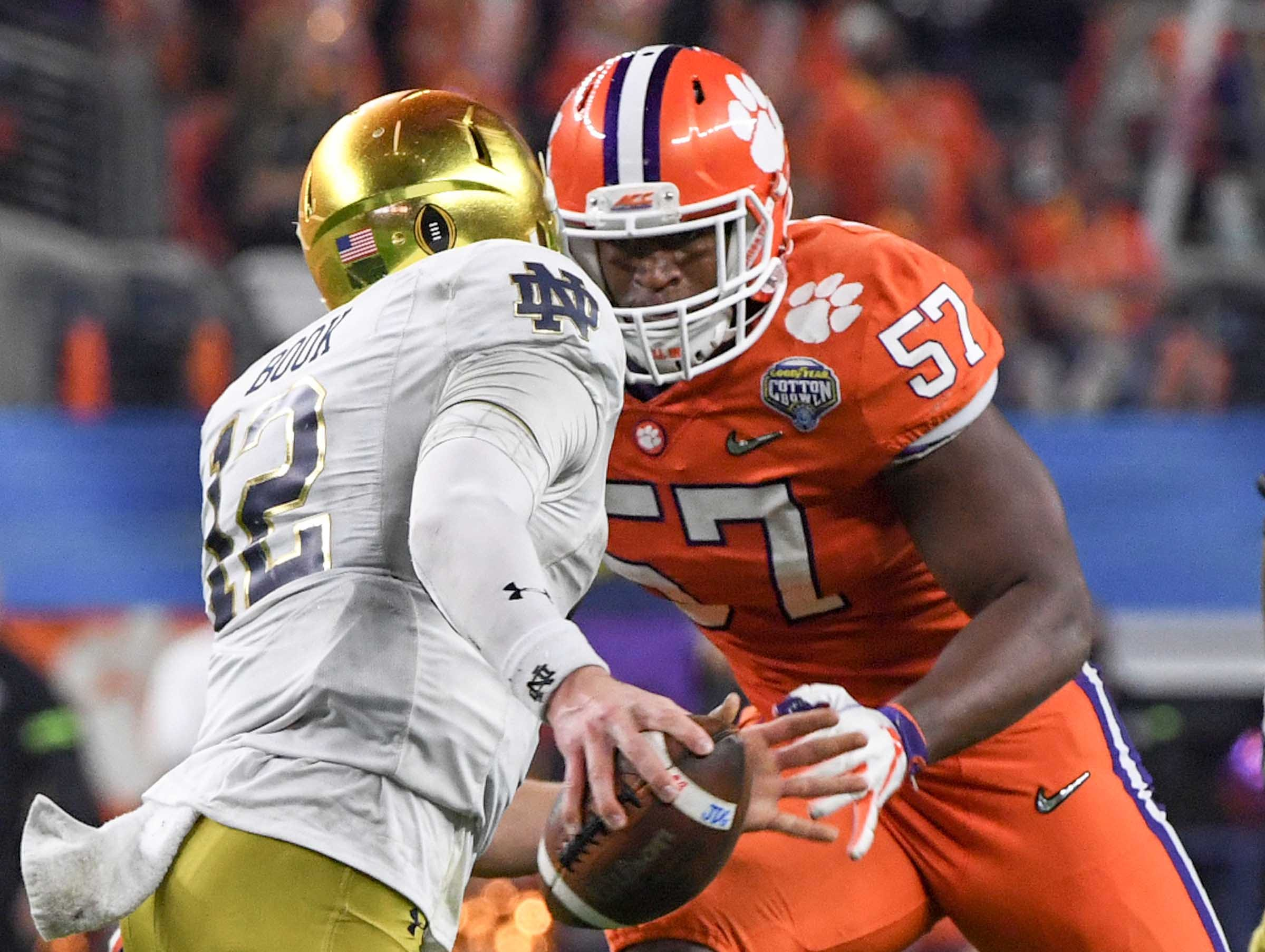 Notre Dame quarterback Ian Book (12) runs from Clemson linebacker Tre Lamar (57) during the fourth quarter of the College Football Playoff Semifinal at the Goodyear Cotton Bowl Classic at AT&T Stadium in Arlington, Texas Saturday, December 29, 2018.