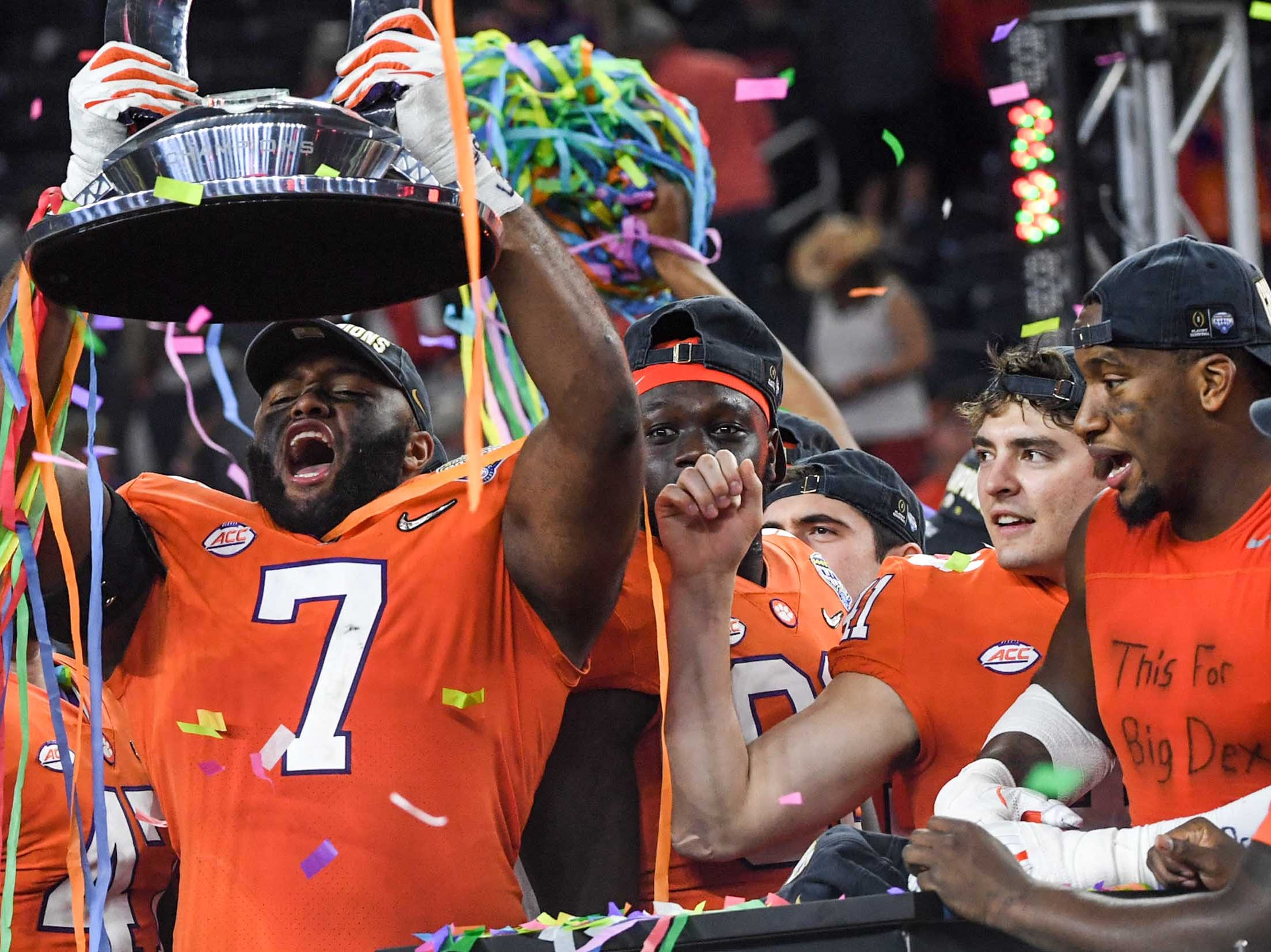 """Clemson defensive lineman Austin Bryant (7), left, holds up the Cotton Bowl trophy near defensive lineman Clelin Ferrell (99), right, wearing an undershirt with handwritten words """"This For Big Dex"""", after their 30-3 win over Notre Dame in the College Football Playoff Semifinal at the Goodyear Cotton Bowl Classic at AT&T Stadium in Arlington, Texas Saturday, December 29, 2018."""
