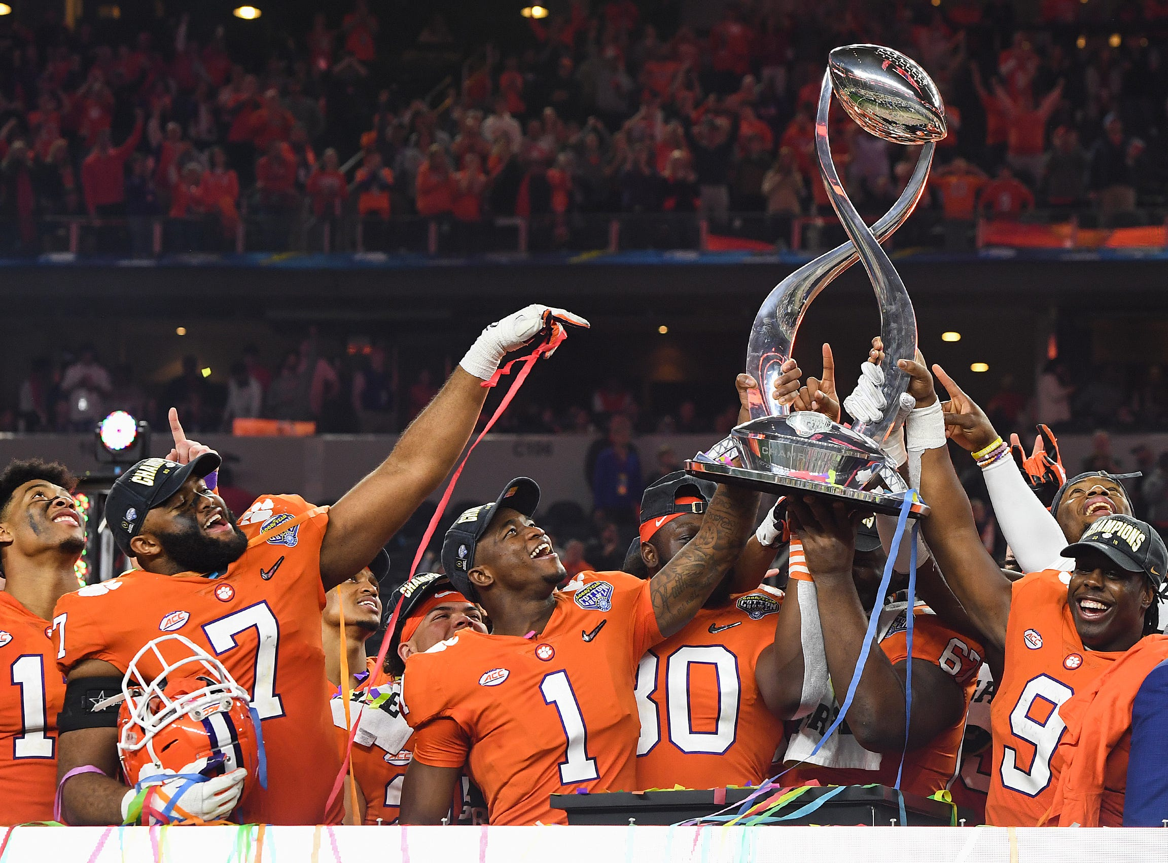 Clemson players cornerback Trayvon Mullen (1), tight end Milan Richard (80), defensive lineman Albert Huggins (67), and running back Travis Etienne (9) hold the Goodyear Cotton Bowl trophy after their 30-3 win over Notre Dame at AT&T stadium in Arlington, TX Saturday, December 29, 2018.