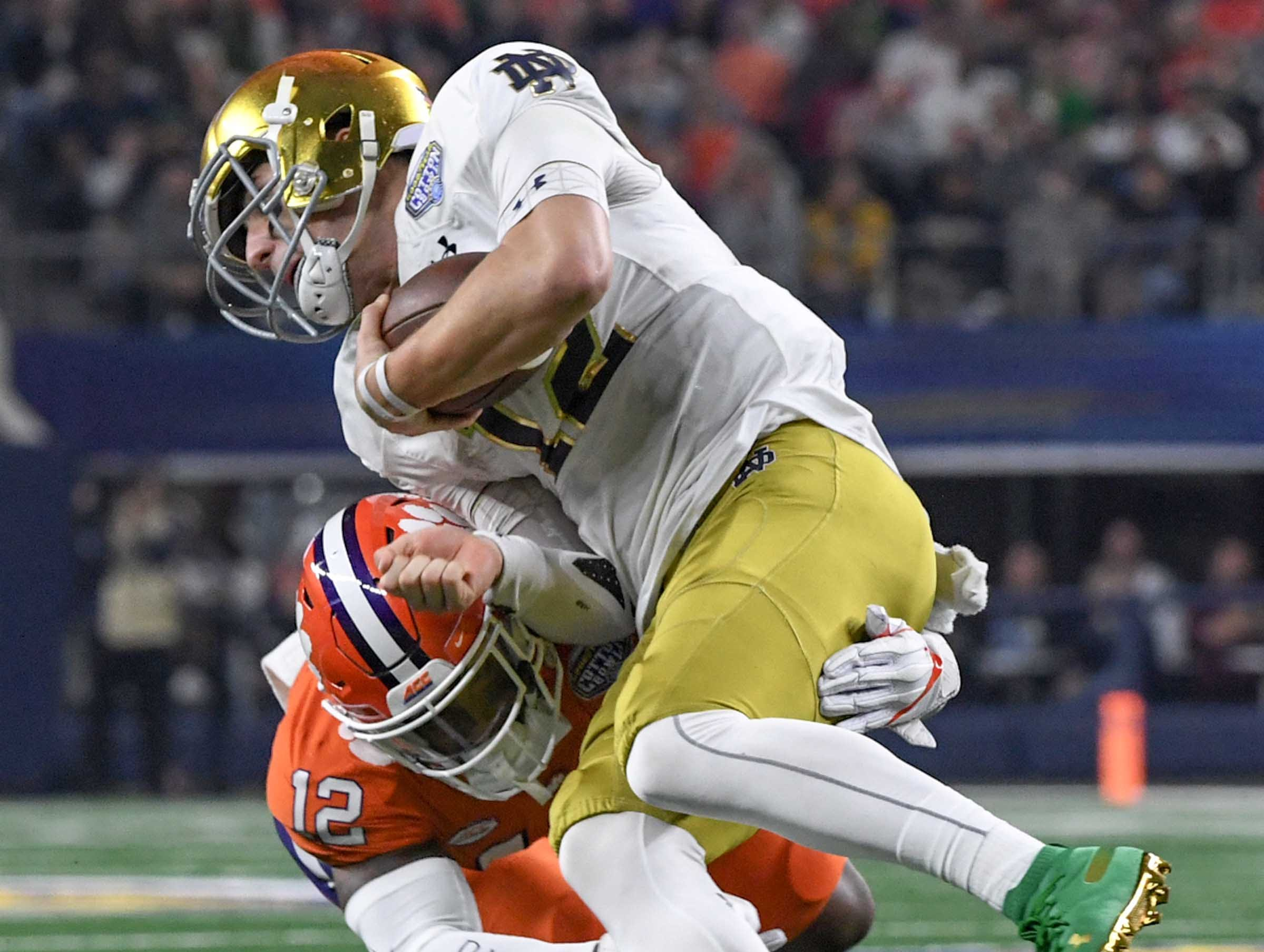 Clemson defensive back K'Von Wallace (12) tackles Notre Dame quarterback Ian Book (12) during the third quarter of the College Football Playoff Semifinal at the Goodyear Cotton Bowl Classic at AT&T Stadium in Arlington, Texas Saturday, December 29, 2018.