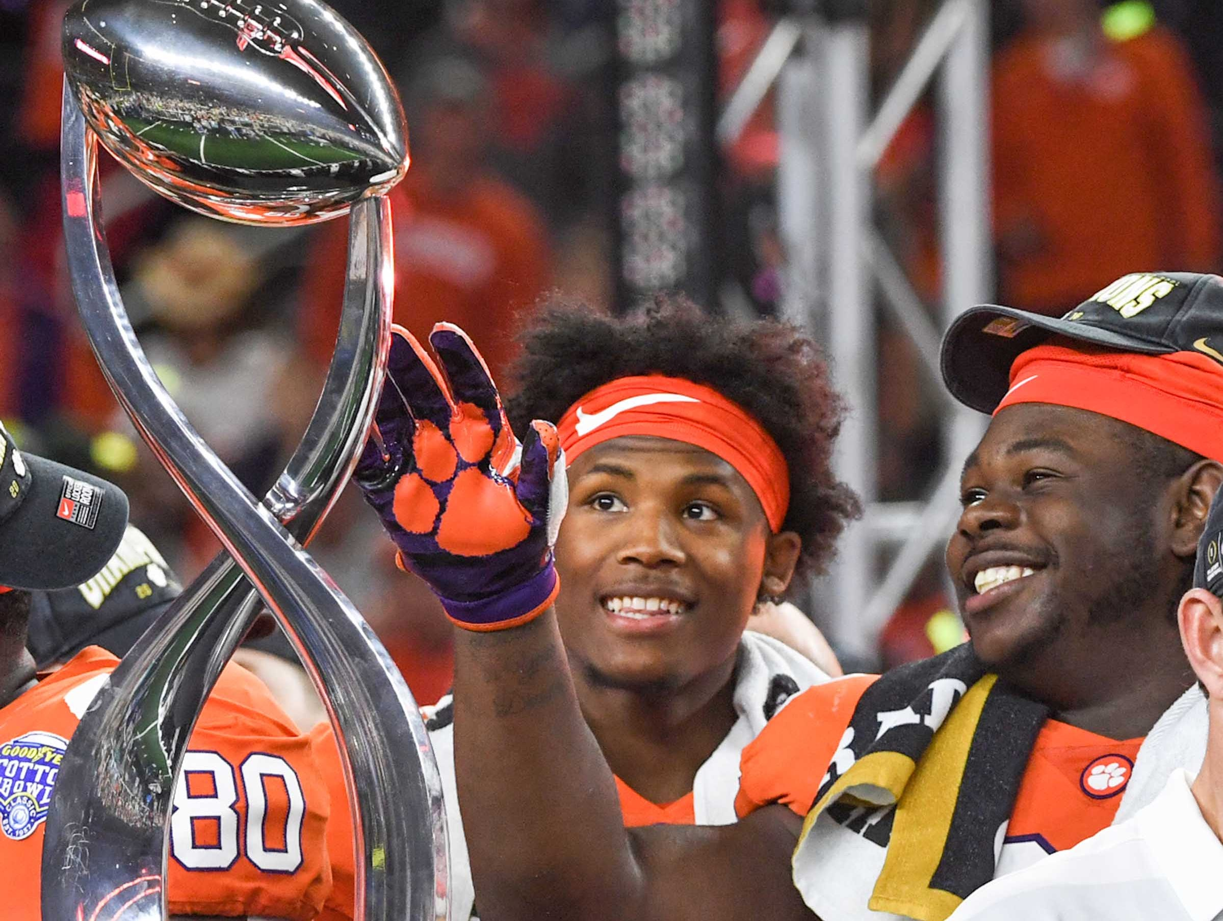 Clemson wide receiver Tee Higgins (5) and defensive lineman Albert Huggins (67) look at the trophy after their 30-3 win over Notre Dame in the College Football Playoff Semifinal at the Goodyear Cotton Bowl Classic at AT&T Stadium in Arlington, Texas Saturday, December 29, 2018.