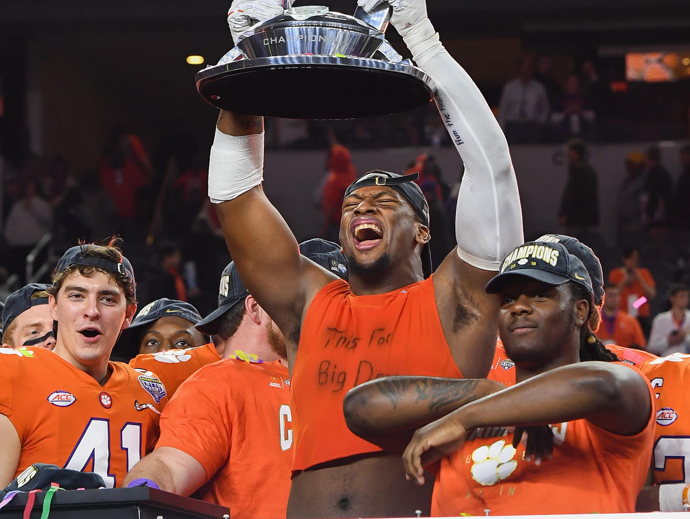 Clemson defensive lineman Clelin Ferrell (99) lifts the Goodyear Cotton Bowl trophy after the Tigers 30-3 win over Notre Dame at AT&T stadium in Arlington, TX Saturday, December 29, 2018.