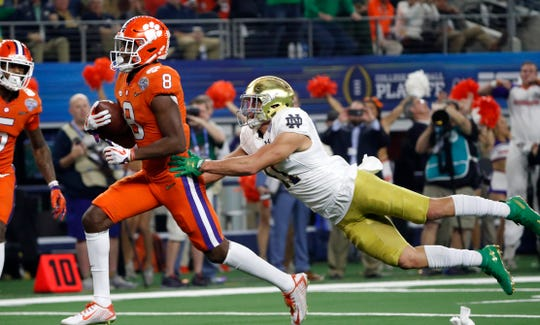 Clemson wide receiver Justyn Ross (8) escapes a tackle attempt by Notre Dame safety Alohi Gilman, right, as Ross reaches the end zone for a touchdown in the first half of the NCAA Cotton Bowl semi-final playoff football game.