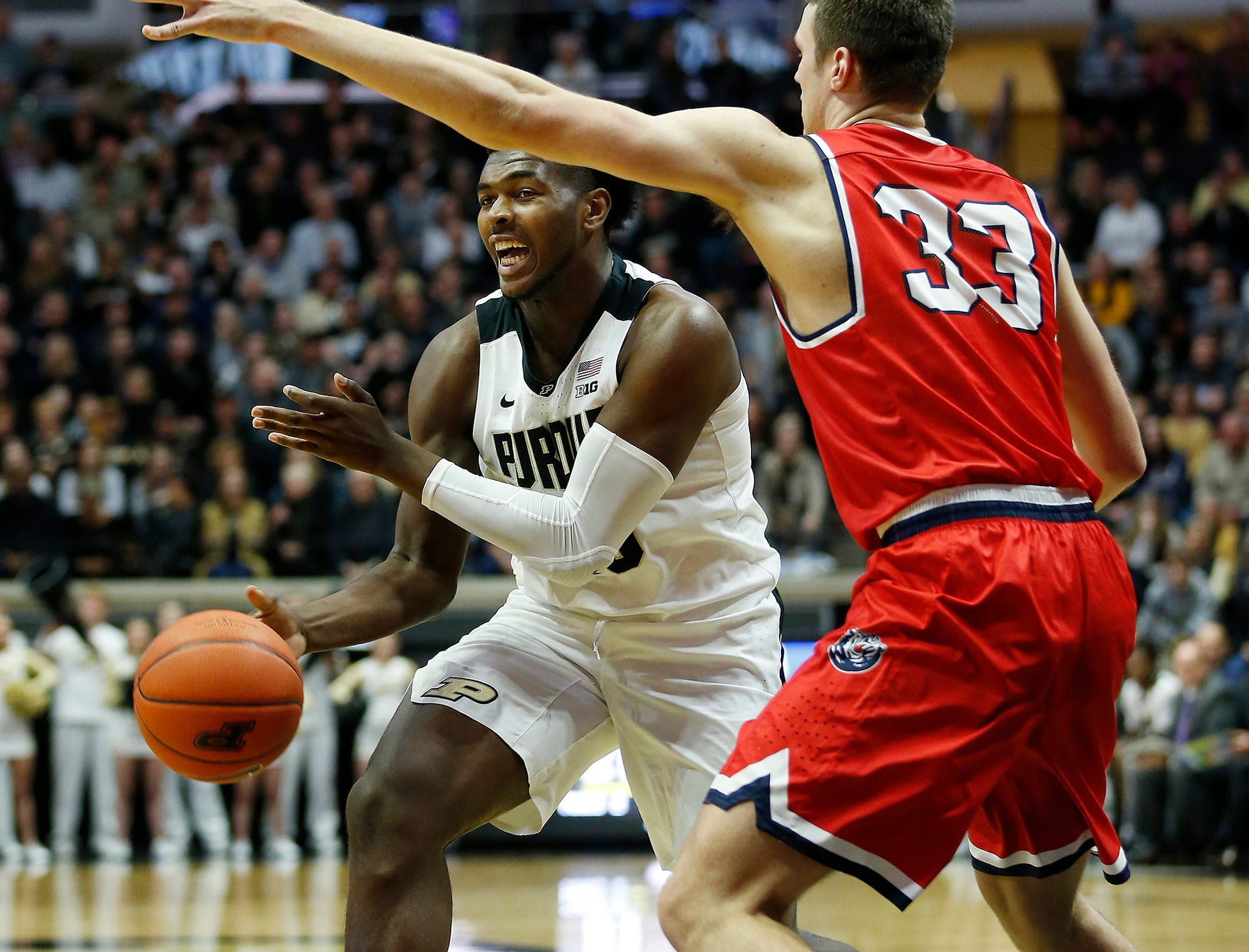Trevion Williams of Purdue slips a pass beneath the arm of Nick Muszynski of Belmont Saturday, December 29, 2018, at Mackey Arena. Purdue defeated Belmont 73-62.