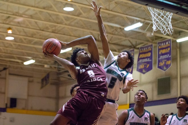 Breaux Bridge's Deandre Hypolite attempts to score over a defender as the Breaux Bridge Tigers take on the Hamilton Christian Warriors at St. Martinville High School on December 29, 2018.