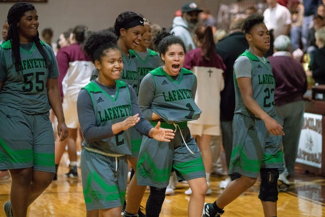 Lafayette High girls basketball team celebrates on the court after beating Vermilion Catholic to win the Yuletide Classic in Abbeville.