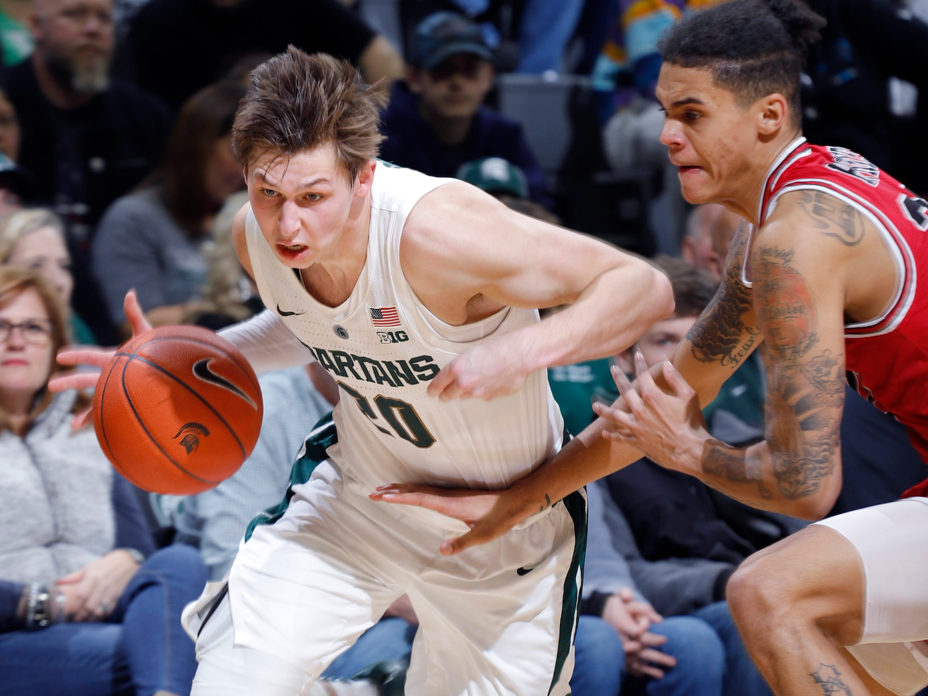 Michigan State's Matt McQuaid, left, drives against Northern Illinois' Rod Henry-Hayes, Saturday, Dec. 29, 2018, in East Lansing, Mich.