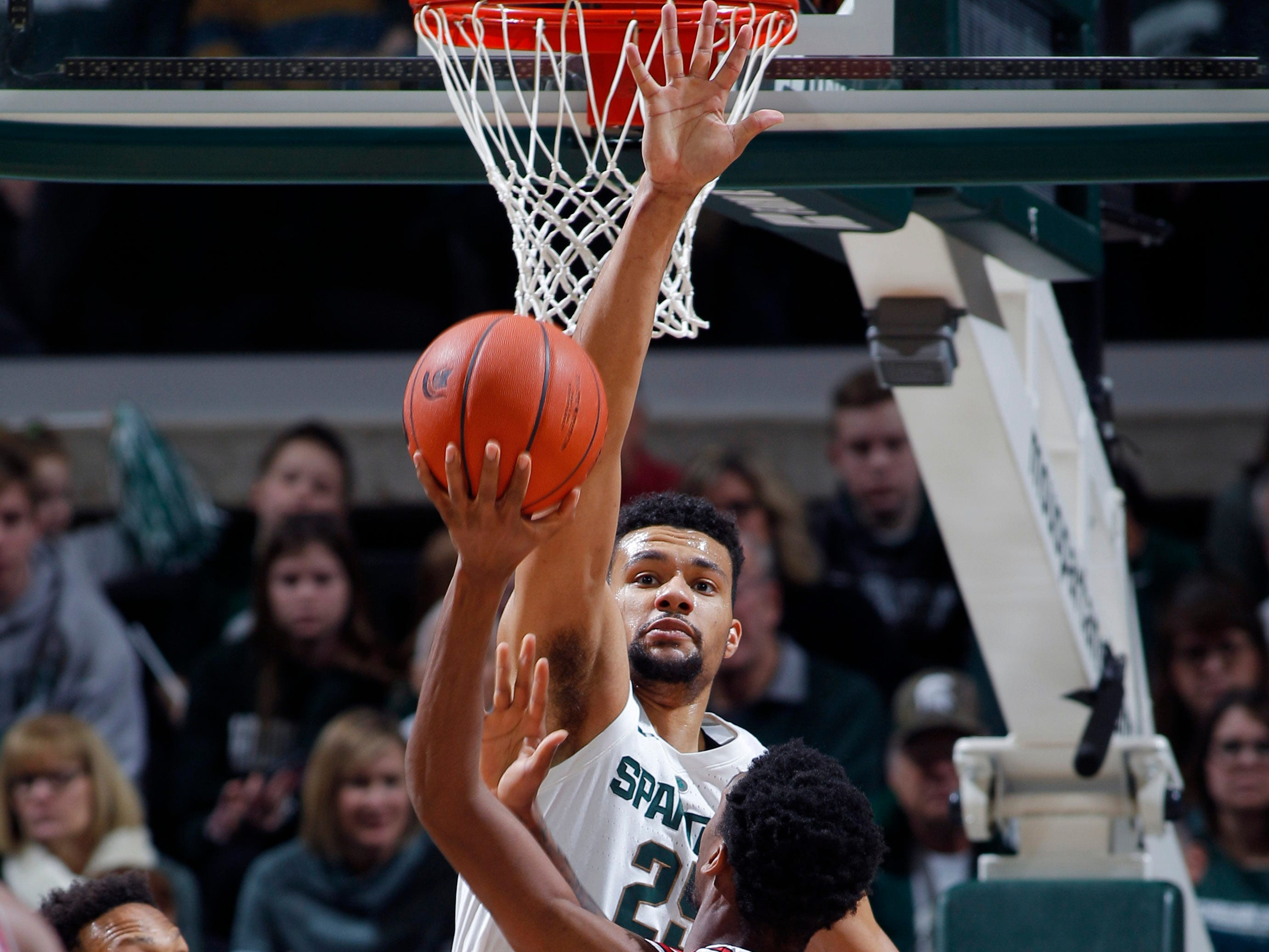 Michigan State's Kenny Goins blocks a shot by Northern Illinois' Levi Bradley as Michigan State's Xavier Tillman (23) and Foster Loyer (3) watch, Saturday, Dec. 29, 2018, in East Lansing, Mich.