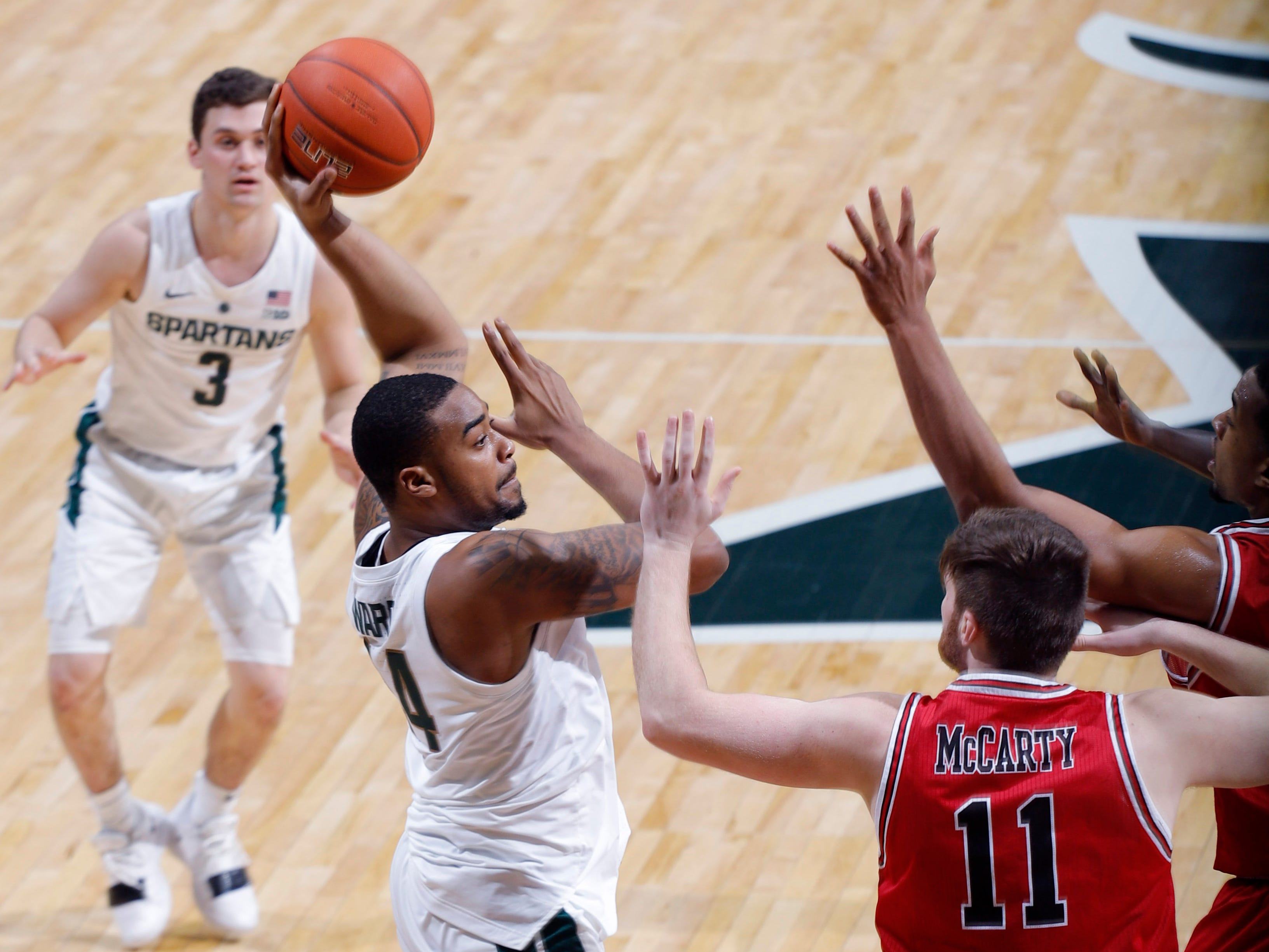 Michigan State's Nick Ward, left, passes out of a double team against Northern Illinois' Noah McCarty (11), Saturday, Dec. 29, 2018, in East Lansing, Mich.