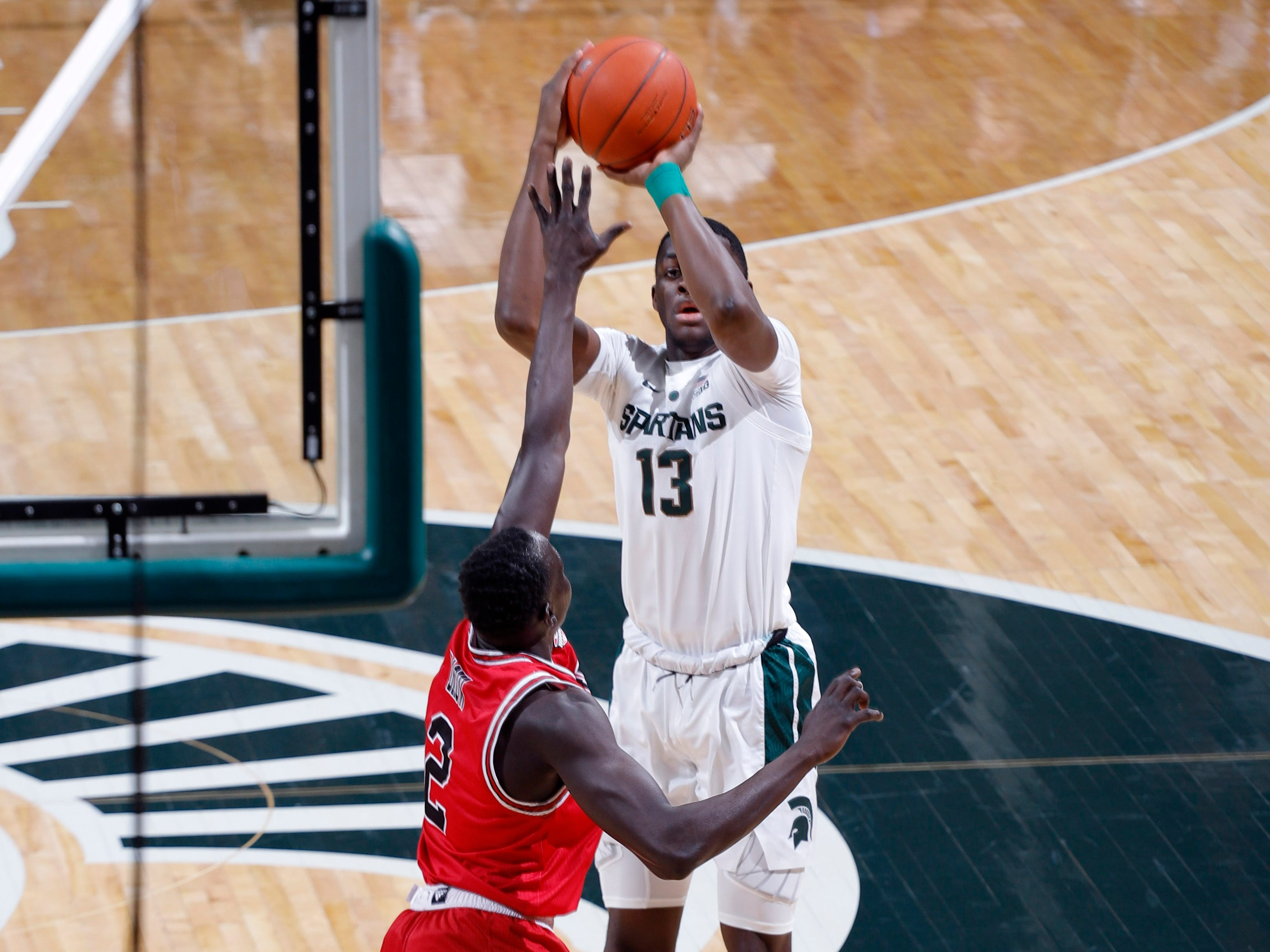 Michigan State's Gabe Brown shoots a 3-pointer against Northern Illinois' Gairges Daow, Saturday, Dec. 29, 2018, in East Lansing, Mich.